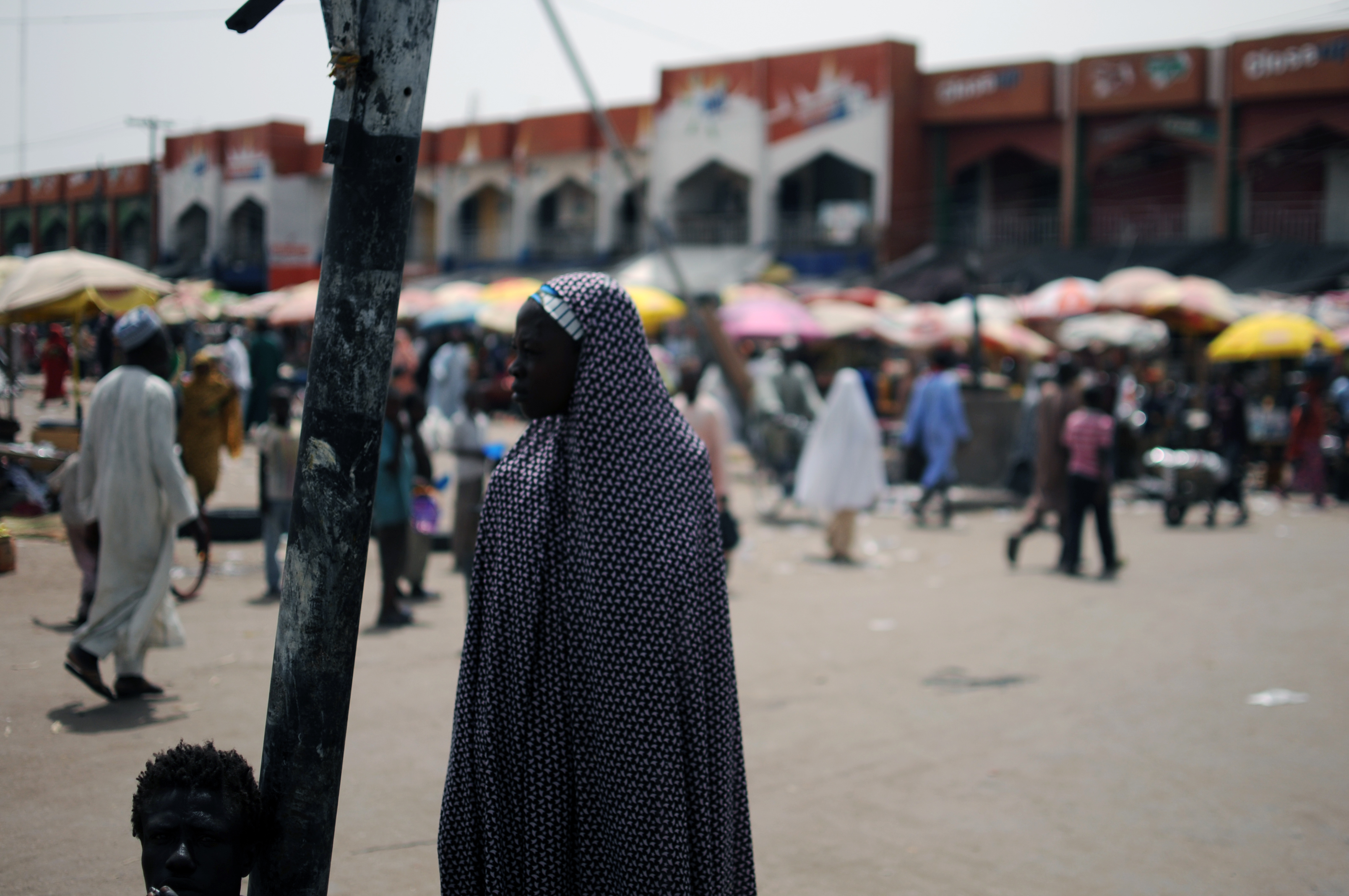 A woman stands at the market  in Maiduguri, the capital of Borno state, Nigeria, on June 6, 2013
