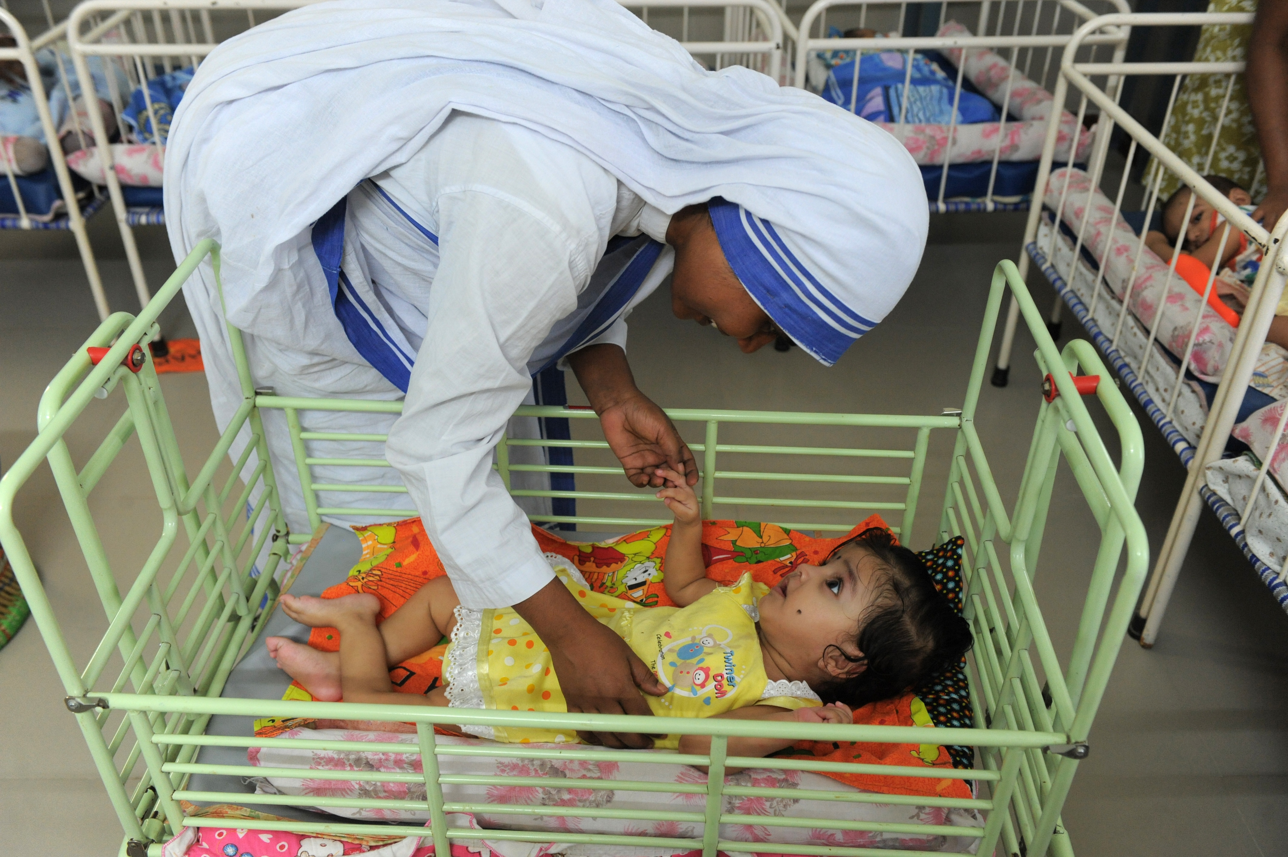 A Christian nun plays with an orphan at Shishu Bhavan, orphanage for discarded babies run by The Missionaries of Charity in Ahmedabad, India, on Sept. 4, 2013.