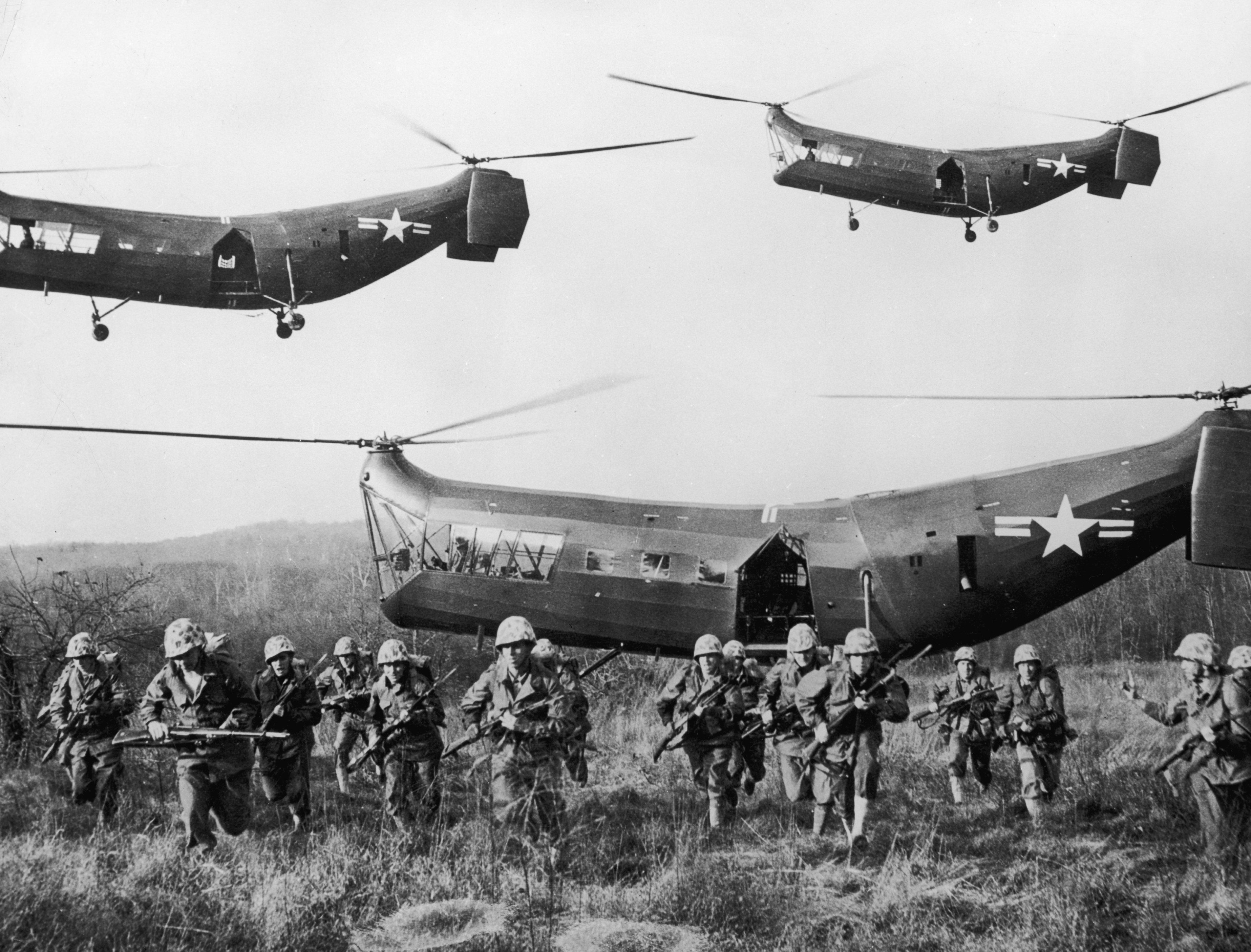 U.S. troops emerge from tandem helicopters onto an open field during the Korean War.