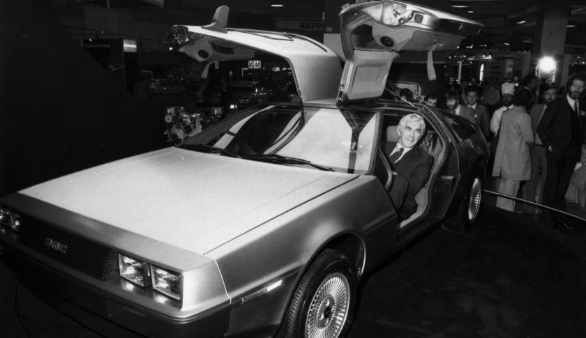 John DeLorean seated in one of his futuristic gull-wing DeLorean DMC-12 sports cars.