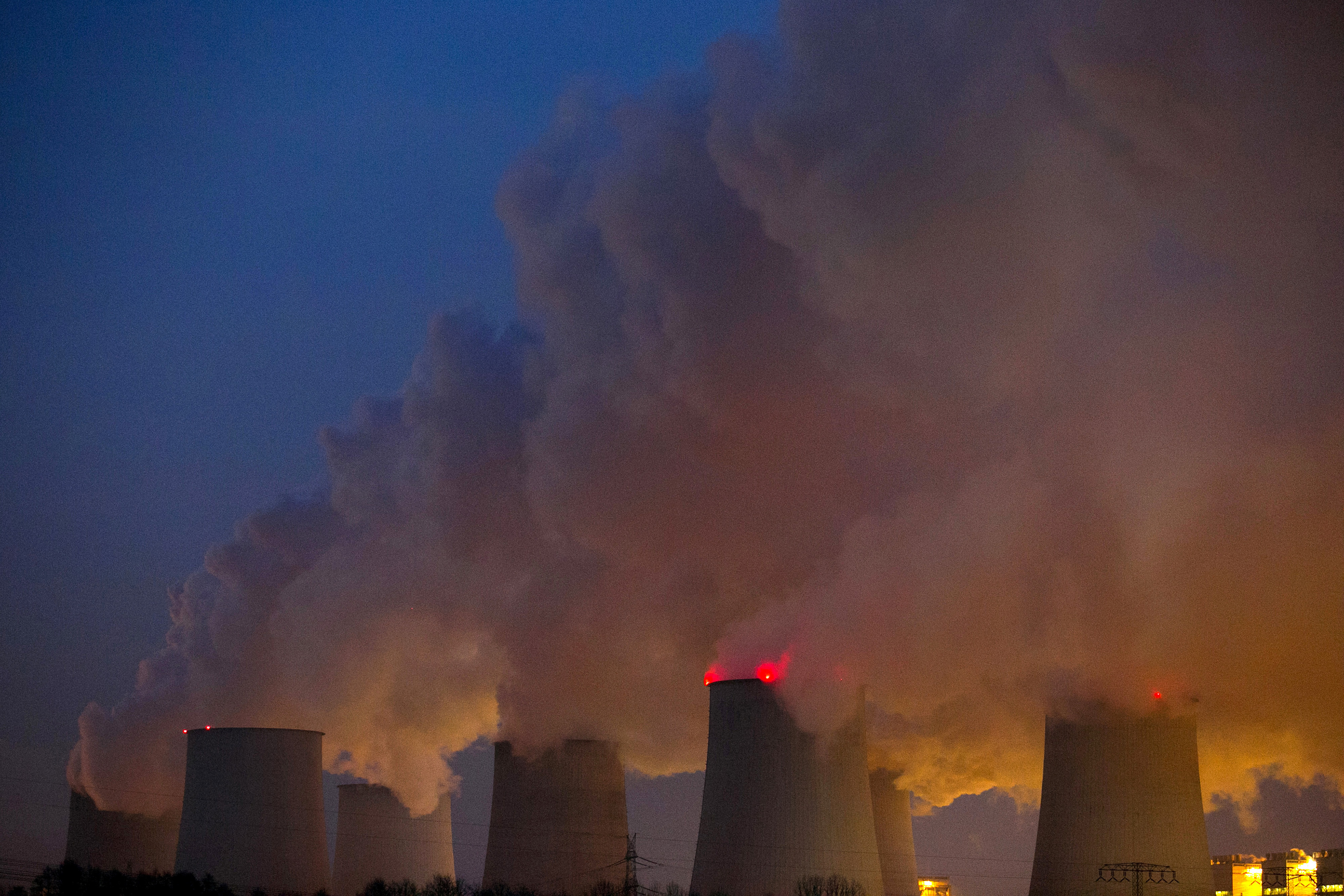 Vapor escapes from cooling towers at the lignite coal-fired power plant operated by Vattenfall AB, in Janschwalde, Germany, on Thursday, Dec. 4, 2014.