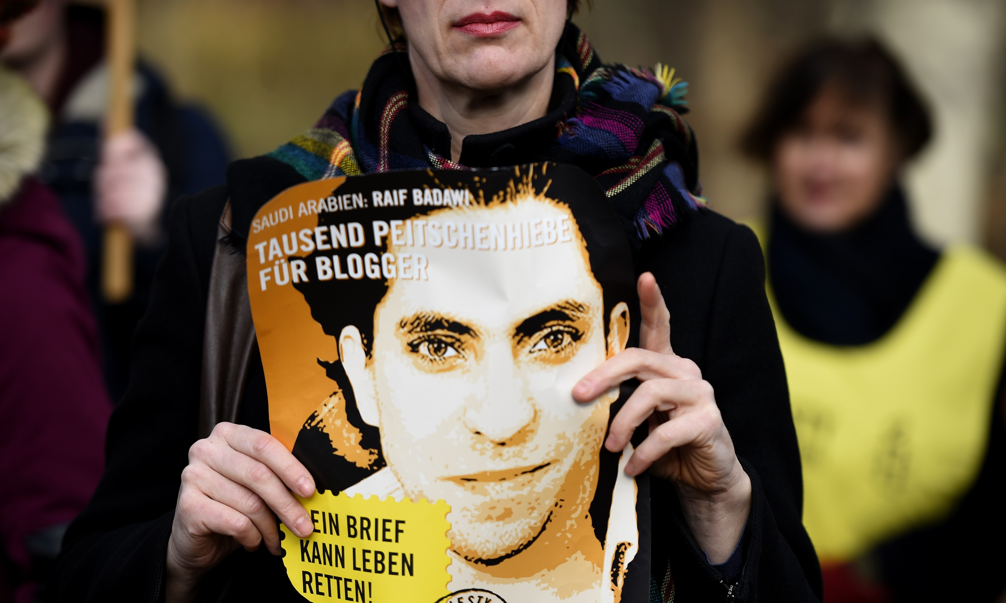 An Amnesty International activist holds a picture of Saudi blogger Raif Badawi during a protest against his flogging punishment on Jan. 29, 2015, in front of Saudi Arabia's embassy in Berlin