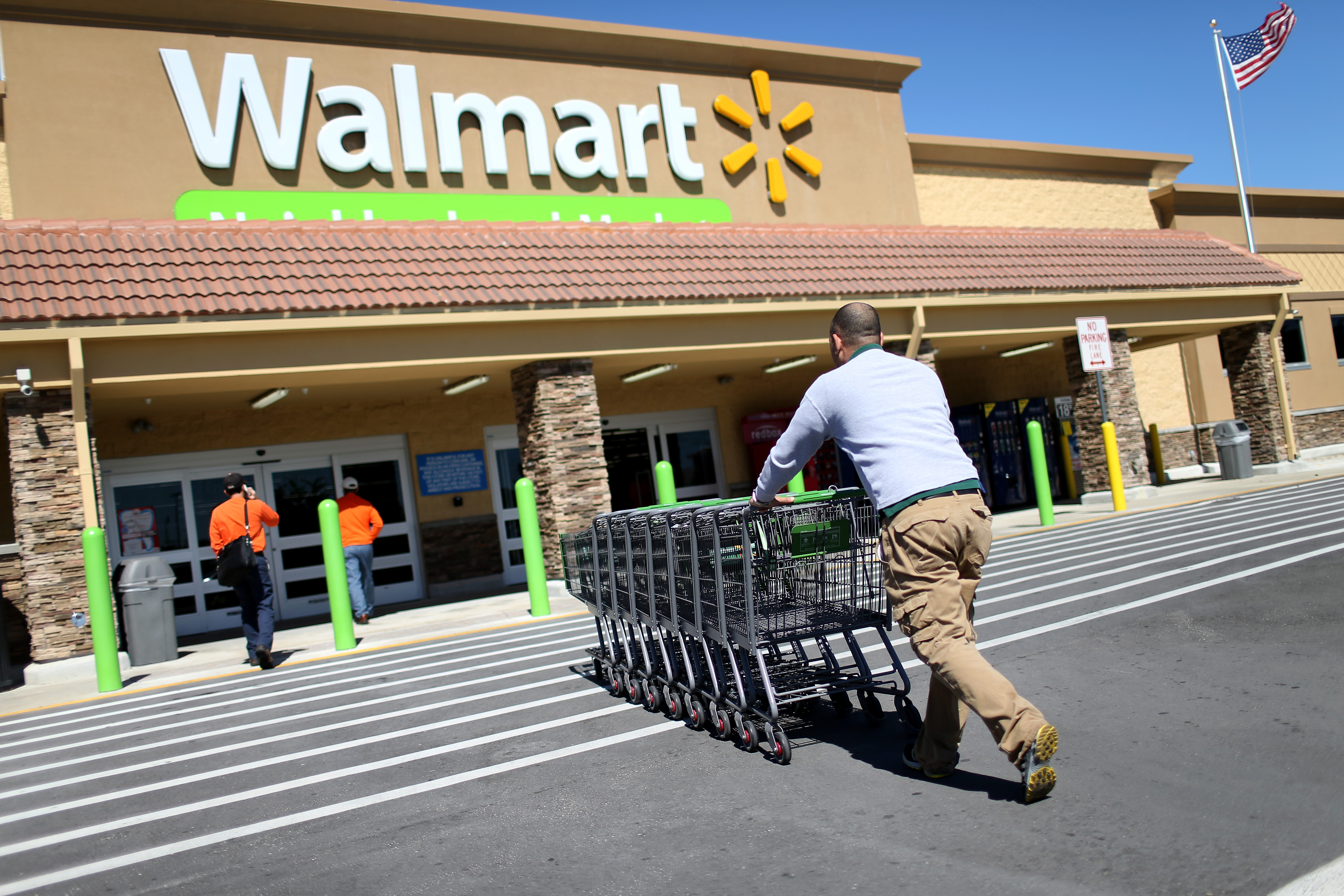 A Walmart employee pushes grocery carts at a Walmart store on February 19, 2015 in Miami, Florida.