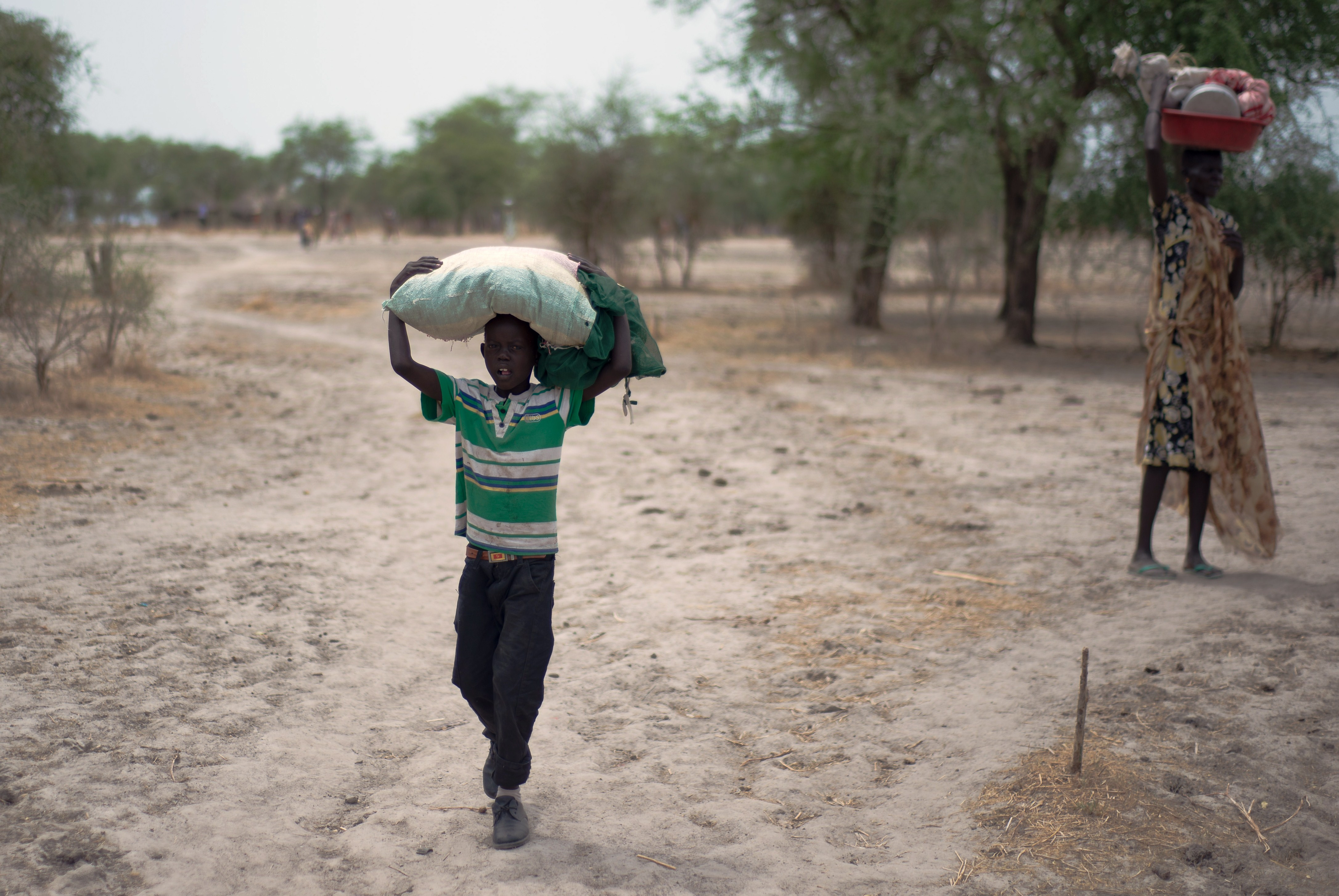 Two Internally Displaced People carry belongings on their heads in Kuernynag in Jonglei State, which borders Upper Nile State and Unity State, on May 2, 2015