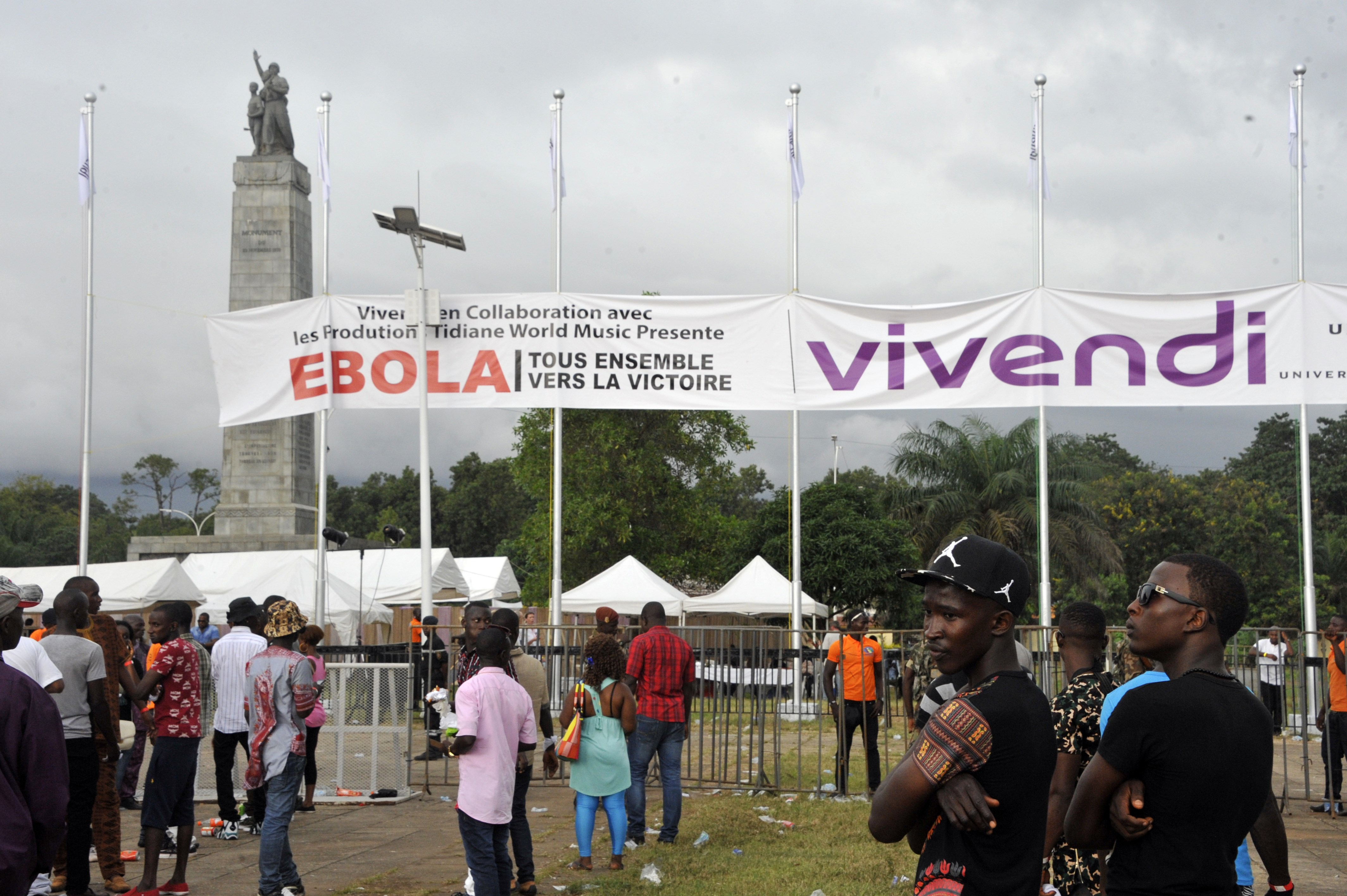 People stand under a banner reading in French  Ebola - All together for victory  during a concert gathering artists from across Africa to celebrate Guinea reaching the final stages of the battle with the deadly Ebola epidemic on Sept. 26, 2015 in Conakry.