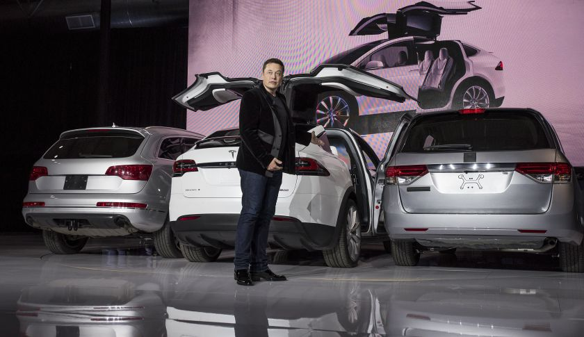 Elon Musk, chairman and CEO of Tesla Motors, demonstrates the 'falcon-wing' doors of the Model X during an event in Fremont, Calif.