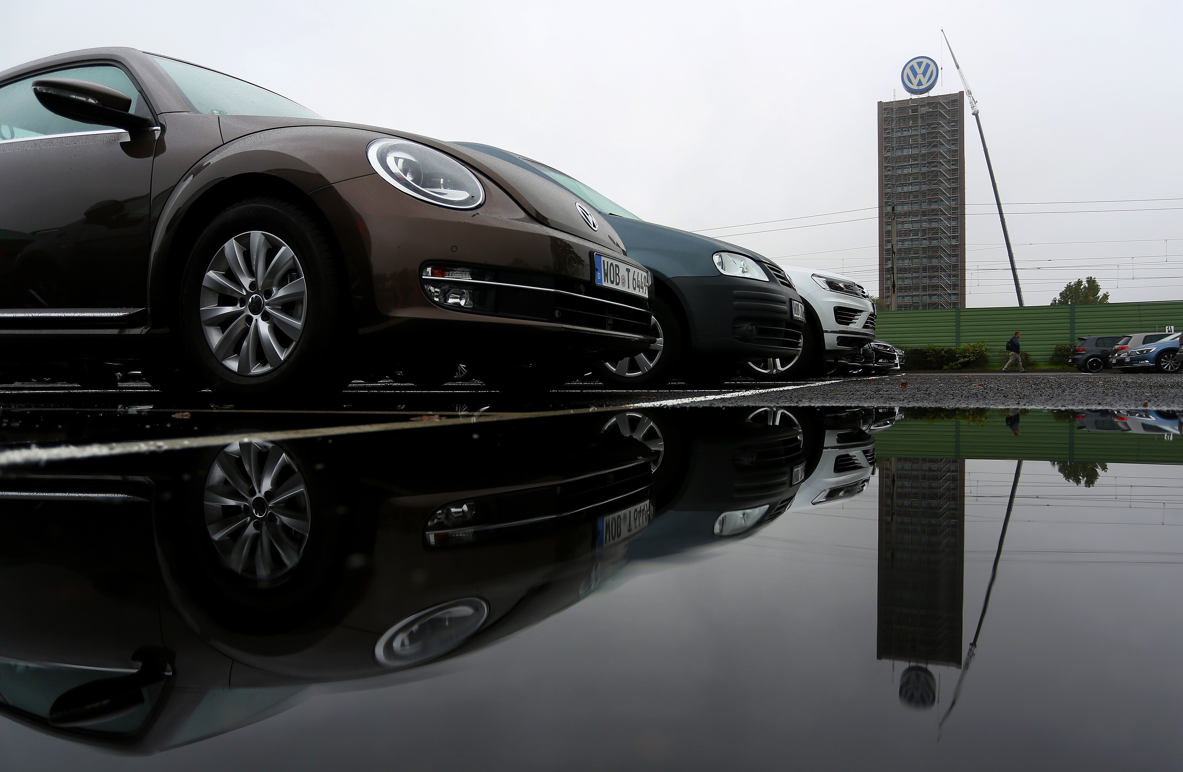 The logo of German carmaker Volkswagen and cars reflect on a rain puddle near the company's headquarters in Wolfsburg, central Germany, on Oct. 8, 2015