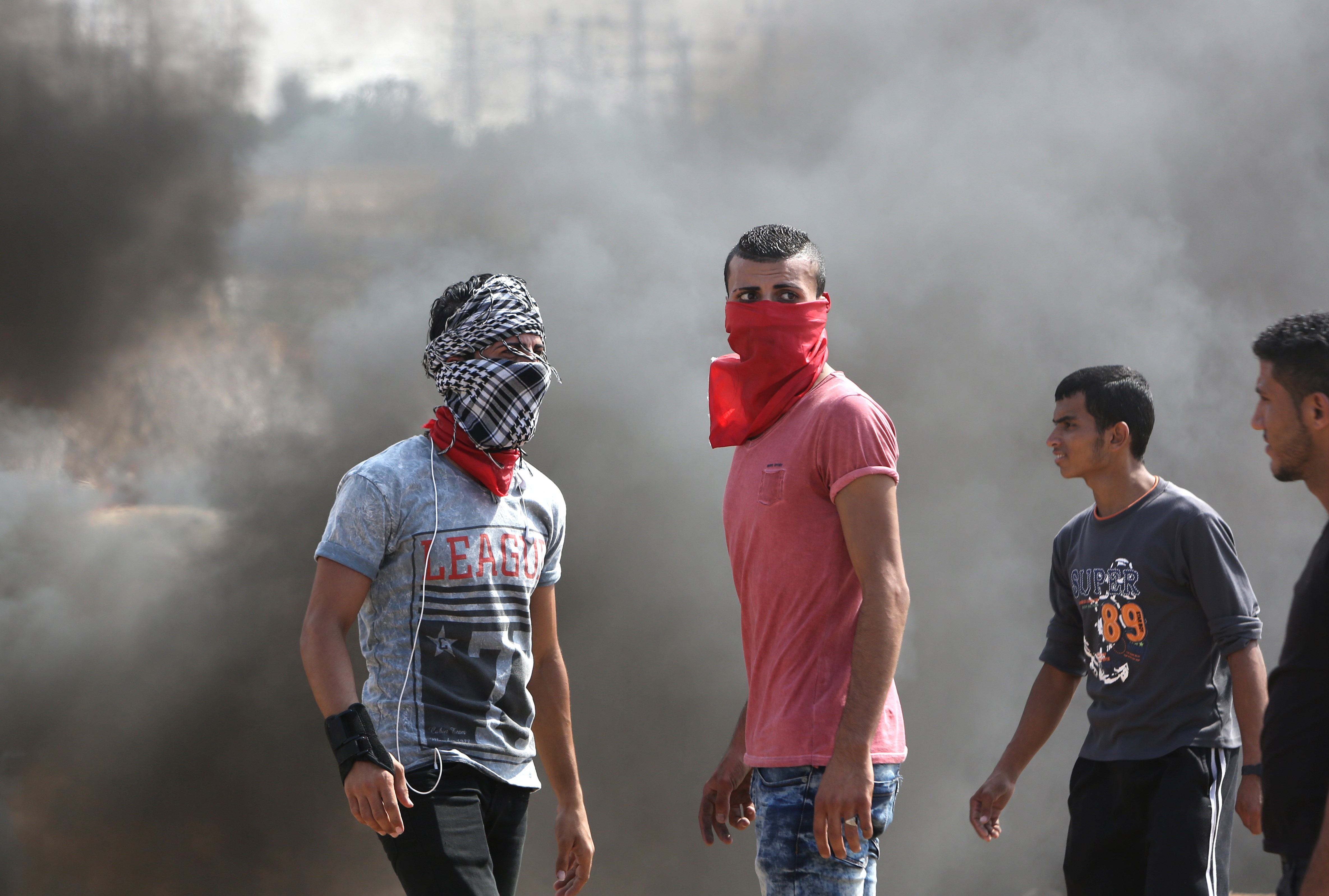 Palestinian protesters stand amid smoke during clashes with Israeli security forces near the Nahal Oz border crossing with Israel, east of Gaza City on Oct. 10, 2015.