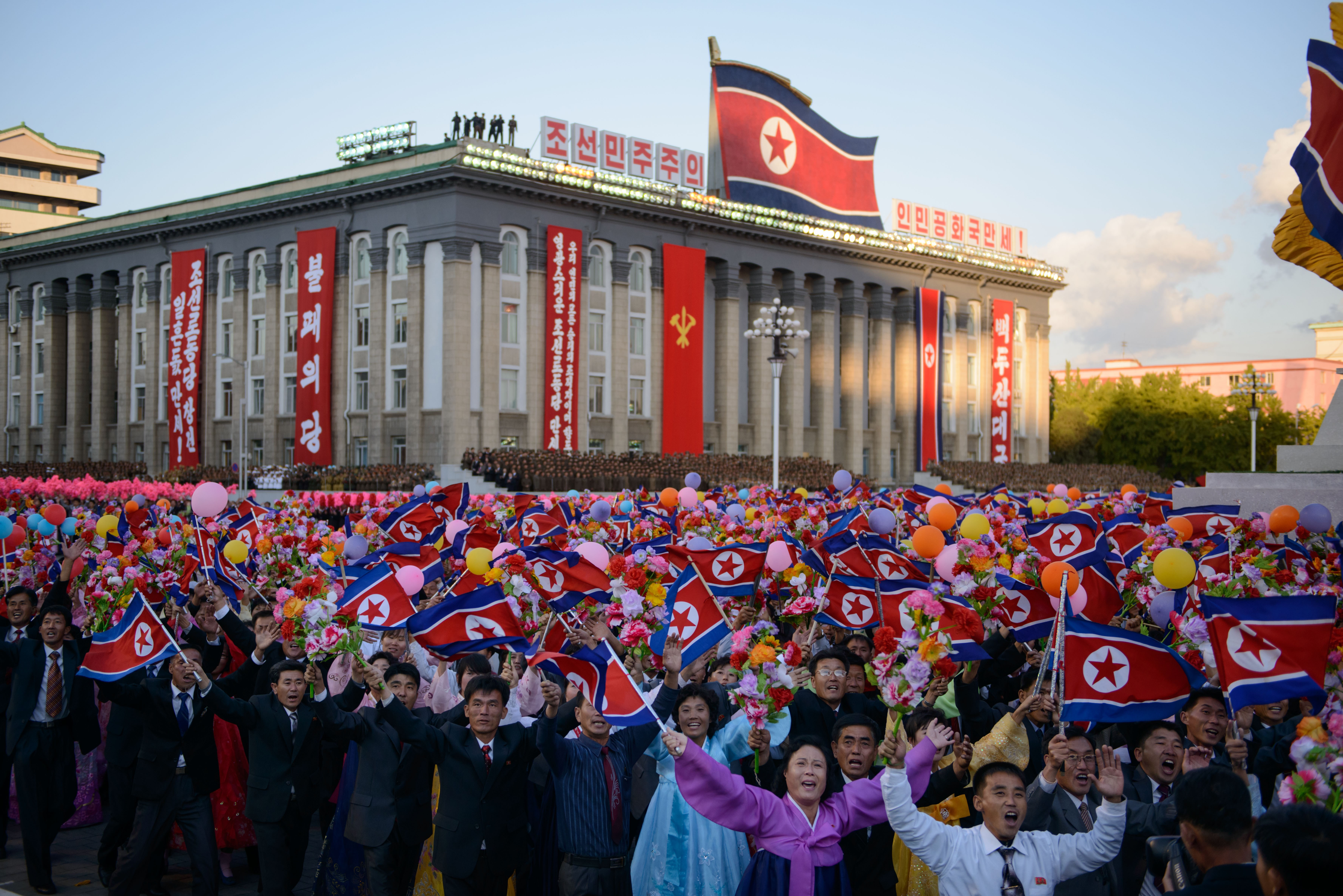 Participants wave flowers towards North Korean leader Kim Jong-Un (not pictured) as they pass through Kim Il-Sung square during a mass military parade in Pyongyang, on Oct. 10, 2015