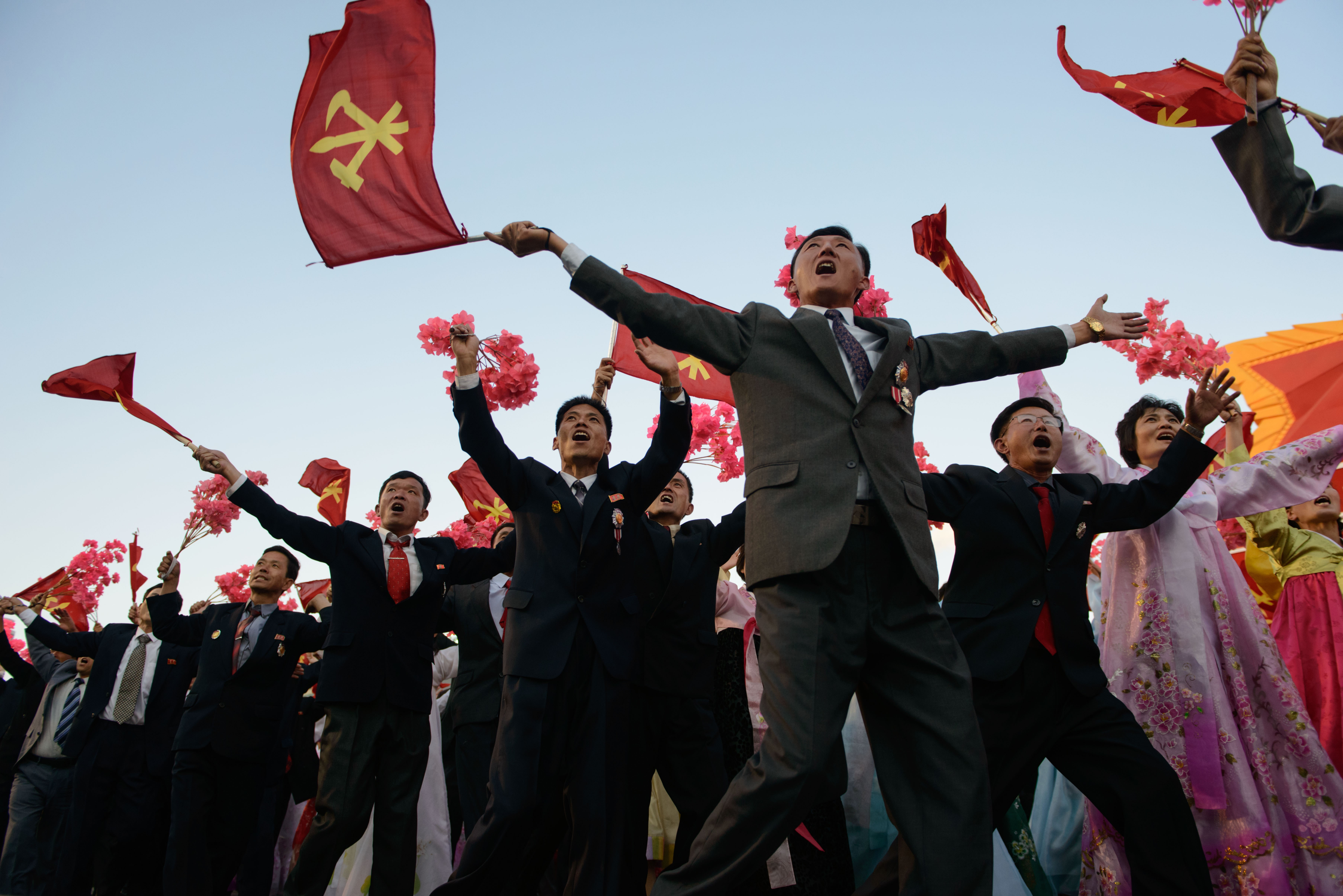 Participants wave flowers towards North Korean leader Kim Jong-Un (not pictured) as they pass through Kim Il-Sung square during a mass military parade in Pyongyang on Oct. 10, 2015.