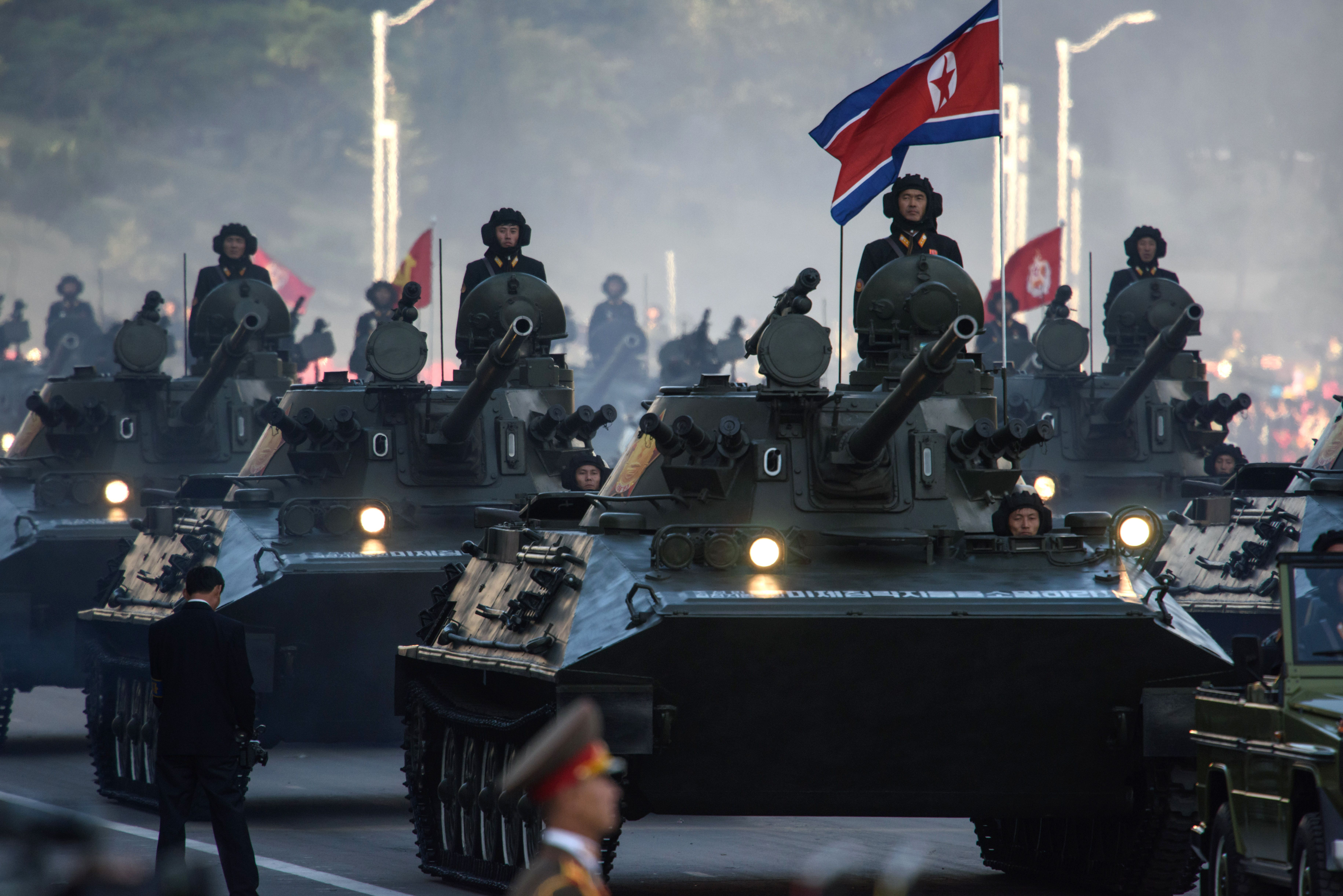 North Korean soldiers ride atop armoured vehicles during a mass military parade at Kim Il-Sung square in Pyongyang on Oct. 10, 2015.