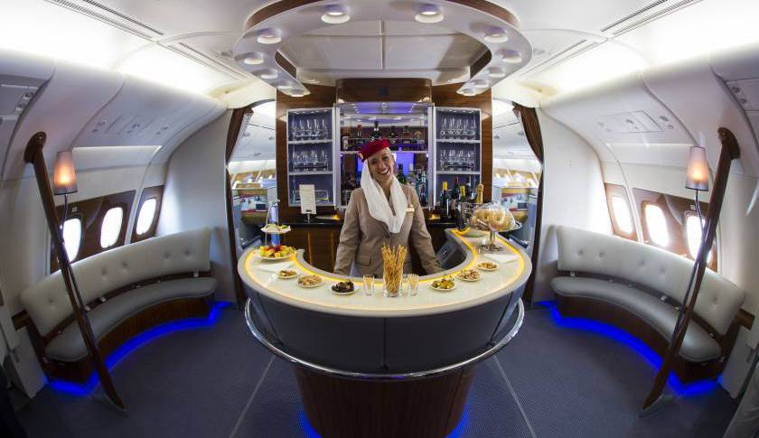 A stewardess poses in the bar of the business class of an Airbus A380 from Emirates.