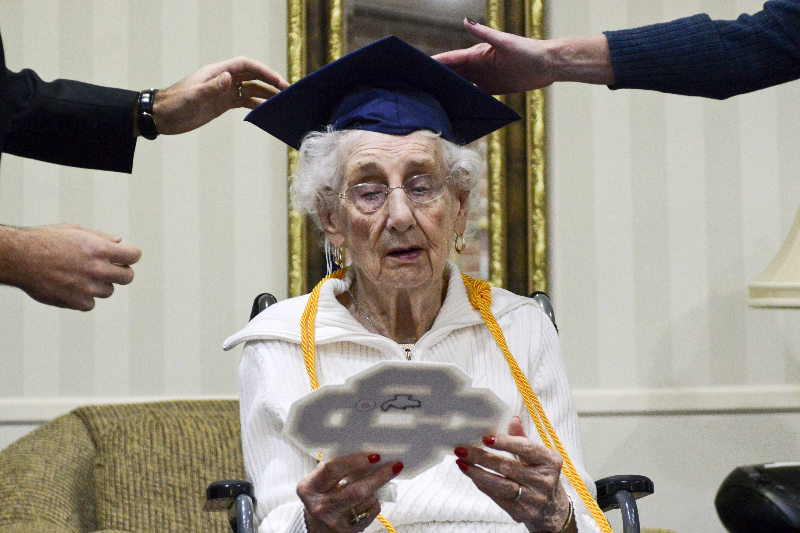 97-year-old Margaret Thome Bekema looks at her high school letter as Catholic Central High School principal Greg Deja, left, and Director of Advancement Beth Banta fix her cap after her honorary graduation at Stonebridge Manor in Grand Rapids, Mich., on Oct. 29, 2015.