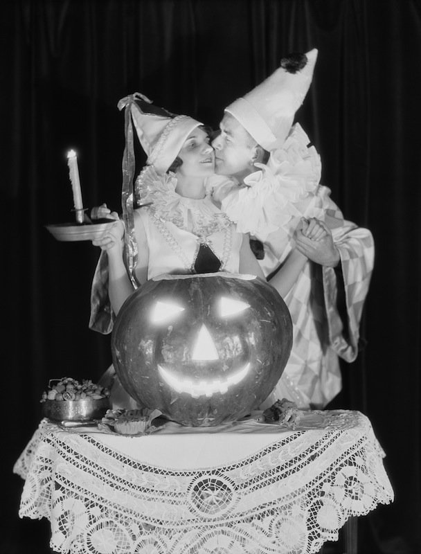 Circa 1920s:  Couple kissing by pumpkin jack-o-lantern candle light.