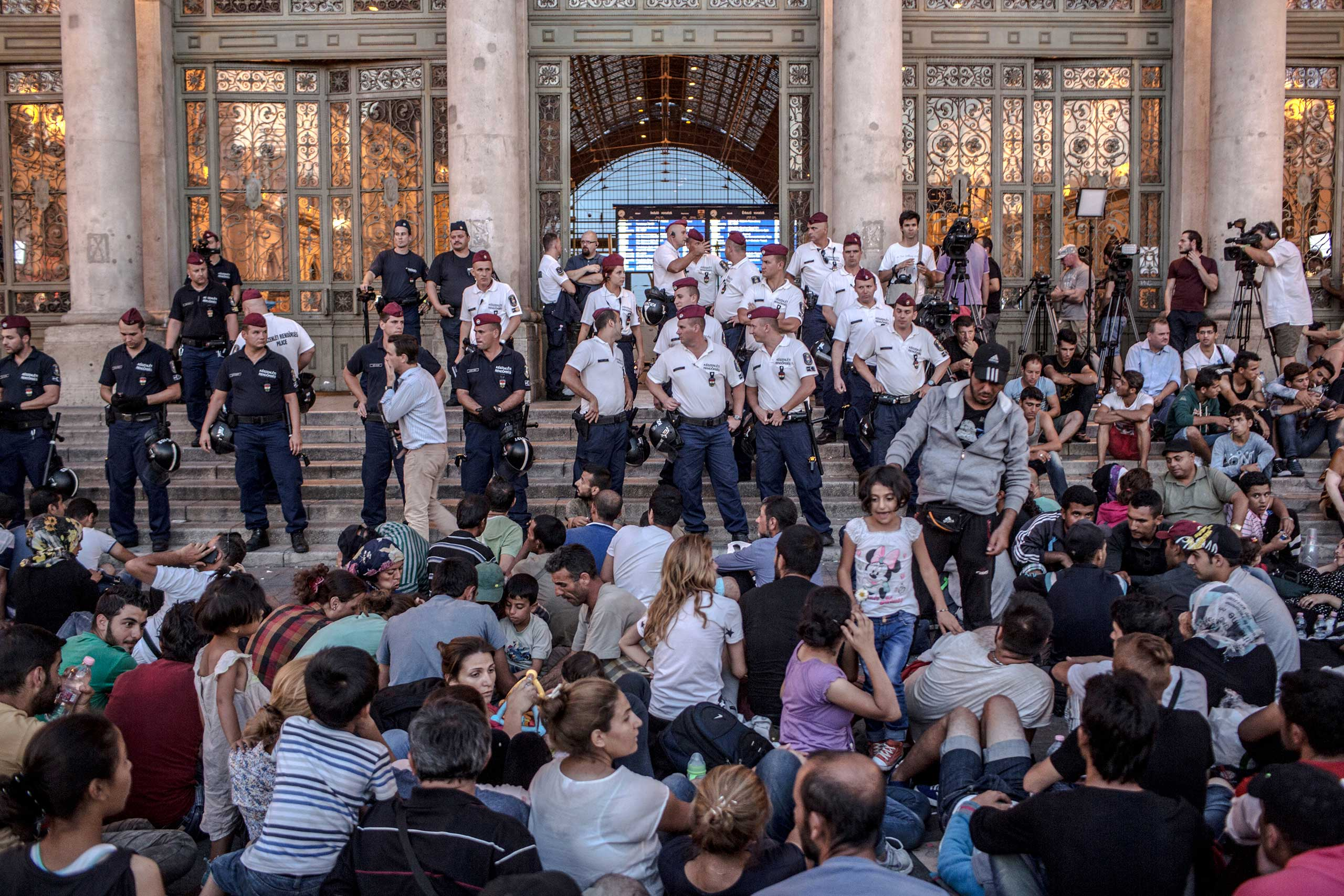 Human Rights Watch: Desperate Journey: Refugees and Asylum Seekers in HungaryHungarian police stand in front of the entrance to the Keleti train station in Budapest, barring entry to the many refugees and asylum seekers who wait to board trains to Germany, on Sept. 1, 2015.