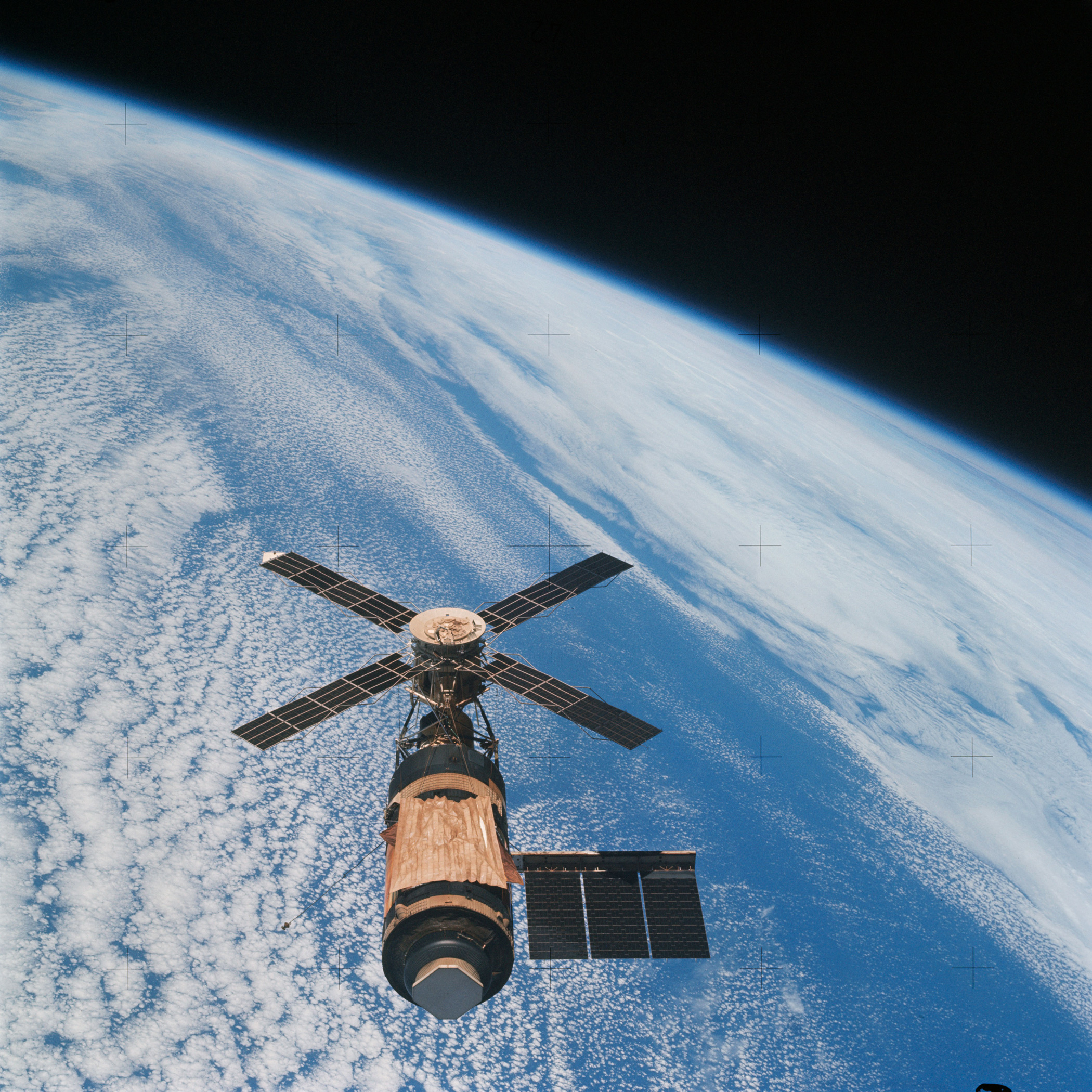 <b>Skylab in Orbit, 1973</b>; An overhead view of the Skylab space station cluster in Earth orbit as photographed from the Skylab 4 Command and Service Modules (CSM) during the final fly-around by the CSM before returning home on May 14, 1973.