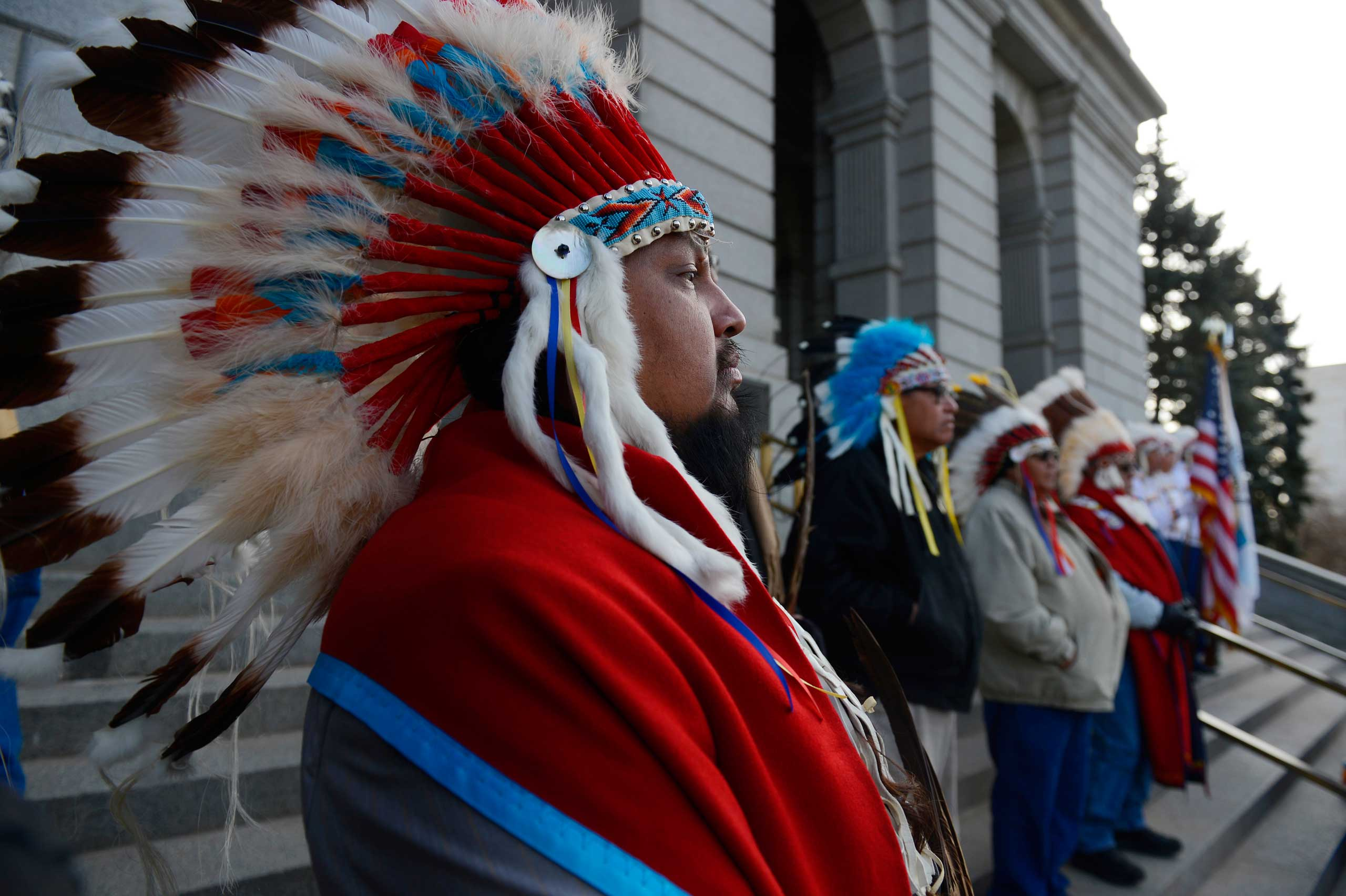 Native American Tribal member, Alan Fletcher, left, Cheyenne and Arapaho tribes, dons a traditional Native American headdress at the west steps of the Colorado Capitol, Dec. 03, 2014.