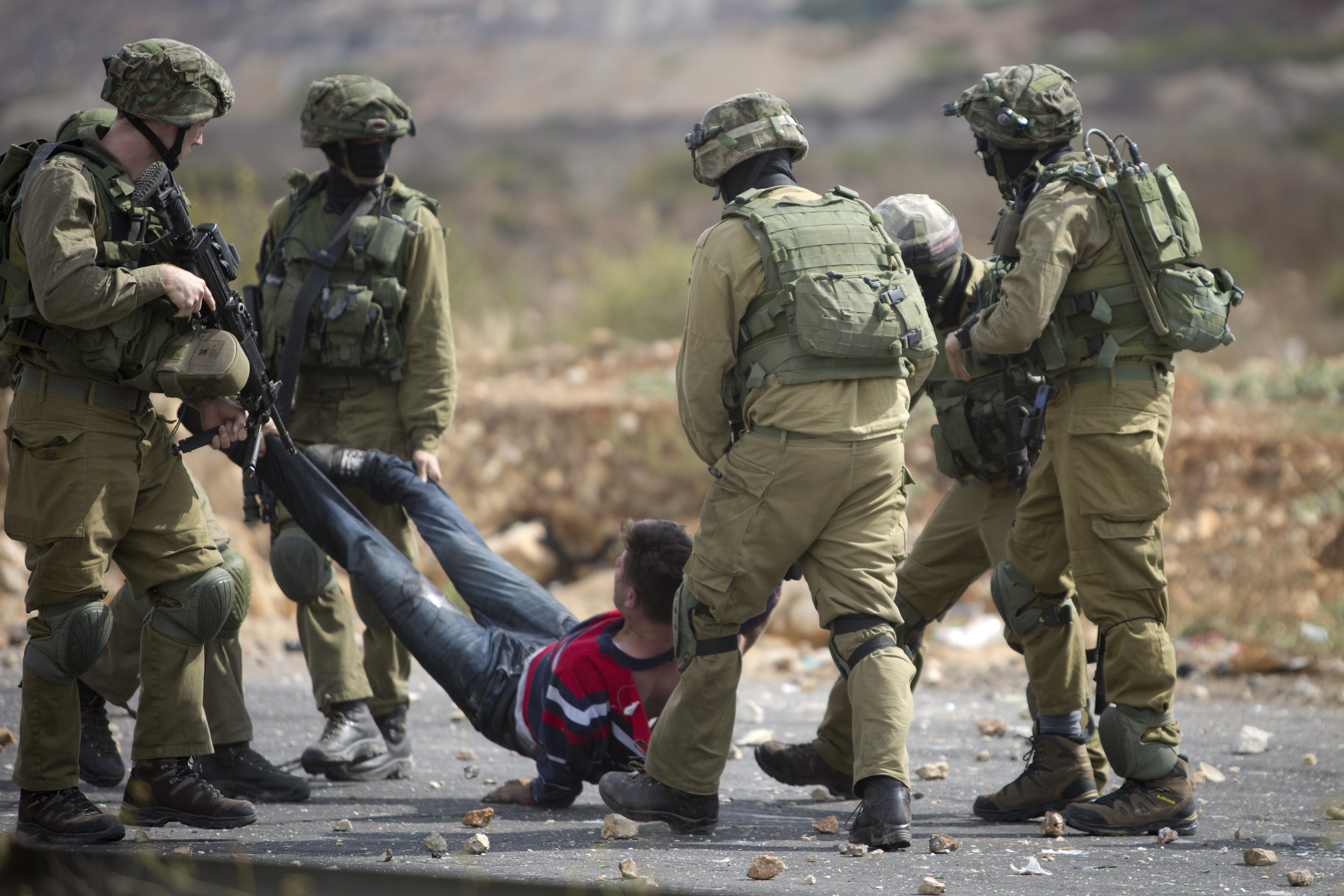 Israeli soldiers carry a Palestinian demonstrator who was wounded by Israeil security forces during clashes near Ramallah, West Bank on Oct. 7, 2015.