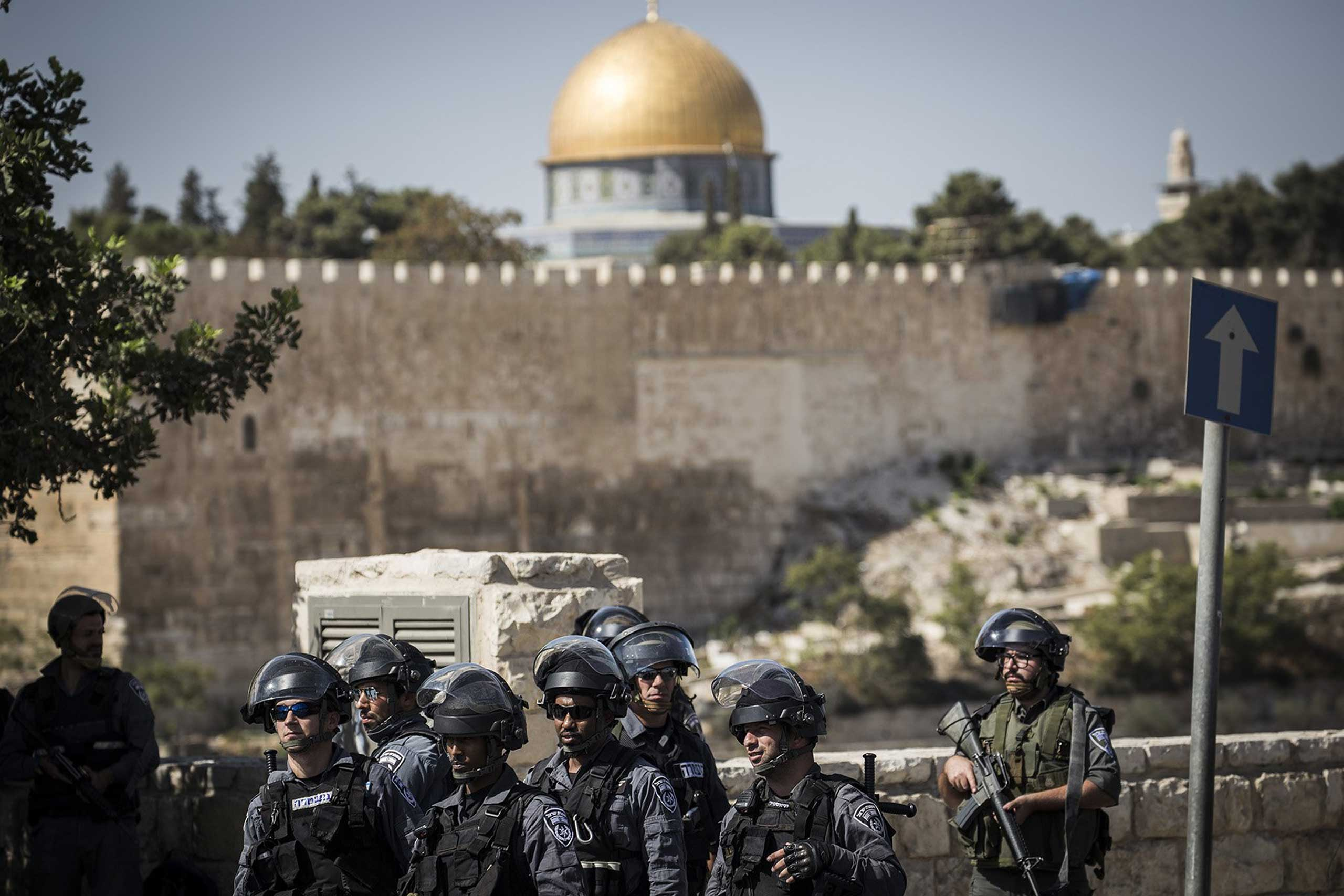 Israeli security forces look on during a noon Friday prayer outside Ras Al Amud neighborhood in Jerusalem, on Oct. 16, 2015.