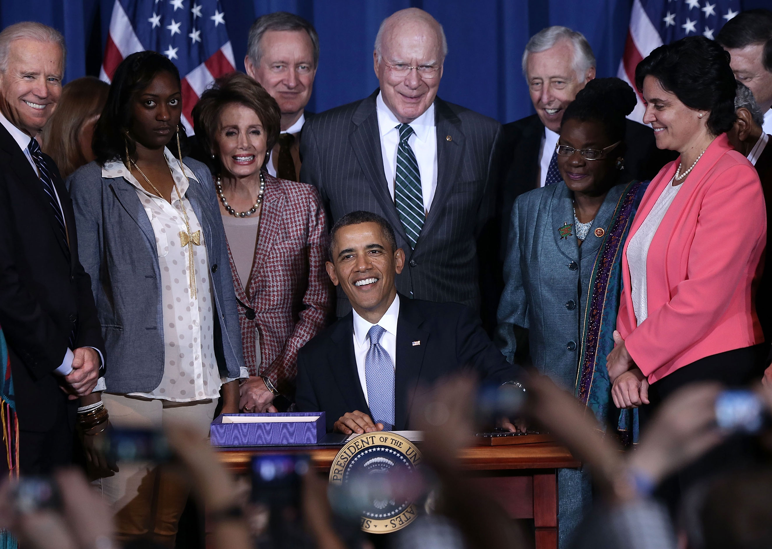 U.S. President Barack Obama (center), joined by (left to right) Vice President Joseph Biden, trafficking survivor Tysheena Rhames, House Minority Leader Representative Nancy Pelosi, Senator Michael Crapo, Senator Patrick Leahy, House Minority Whip Rep. Steny Hoyer, Representative Gwen Moore, and Director of Public Policy of Casa de Esperanza Rosemary Hidalgo-McCabe, signs the Violence Against Women Act into law at the Department of the Interior March 7, 2013 in Washington. The law expanded protections for victims of domestic violence, sexual assault and trafficking.
