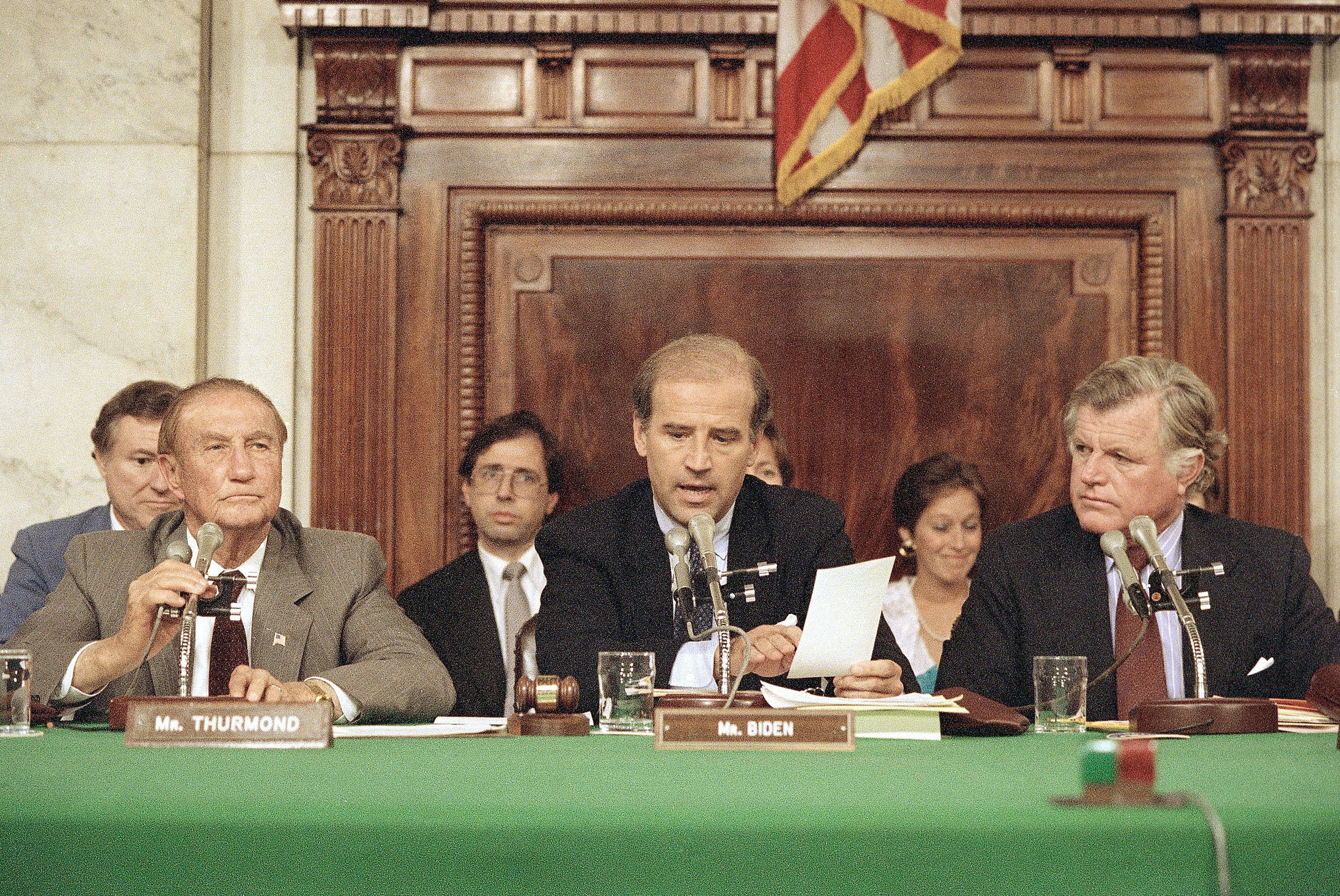 Senate Judiciary Committee Chairman Joe Biden (center) reads from his tally sheet following the committee's voice vote to recommend Robert H. Bork for the Supreme Court on Oct. 6, 1987 in Washington. Senator Strom Thurmond (left) and Senator Edward Kennedy (right) listen.