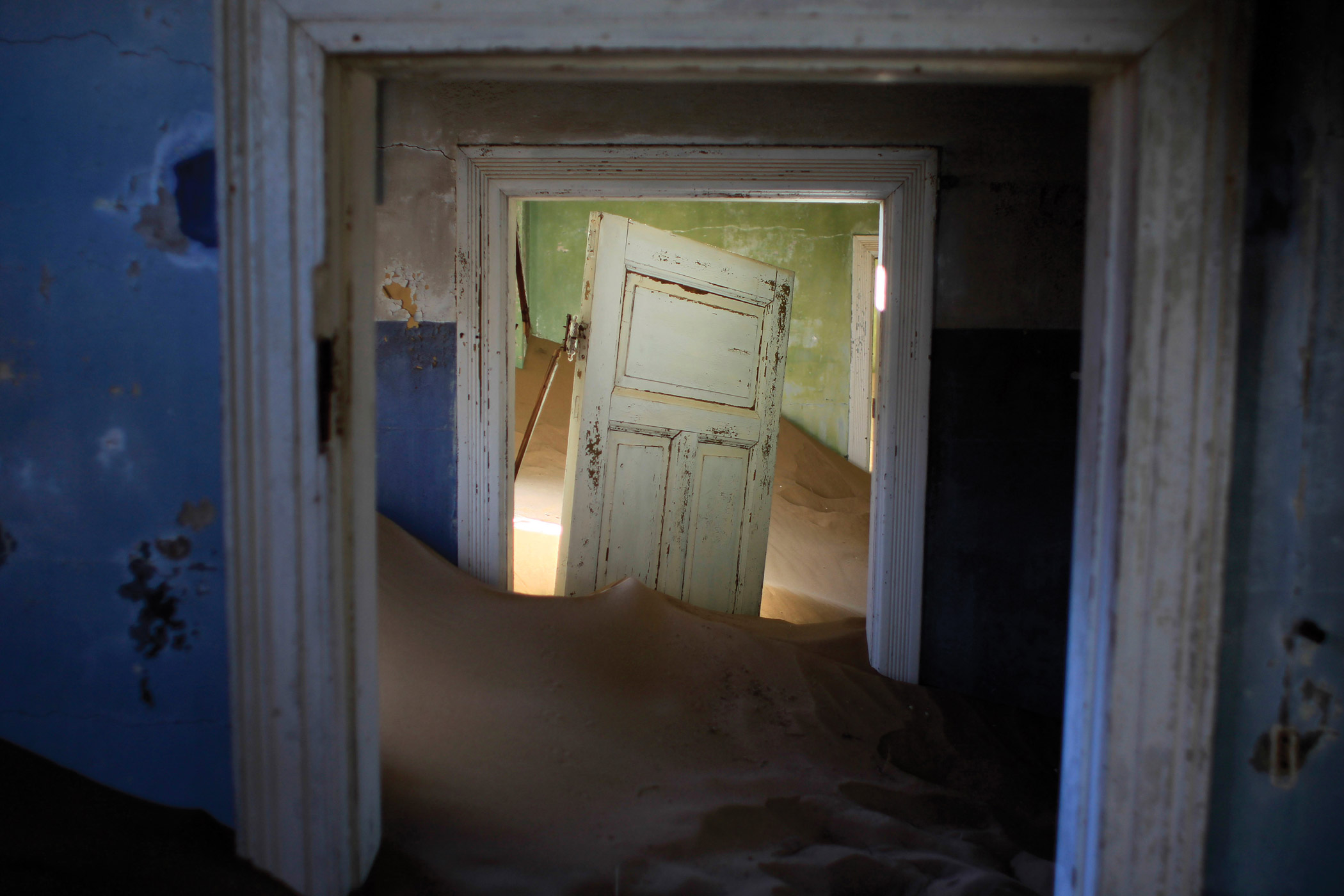 In this July 23, 2013 photo, sand fills an abandoned house in Kolmanskop, Namibia. Kolmanskop, was a diamond mining town south of Namibia, built in 1908 and deserted in 1956. SInce then, the desert slowly reclaims its territory, with sand invading the buildings where 350 German colonists and more than 800 local workers lived during its hay-days of the 1920s.