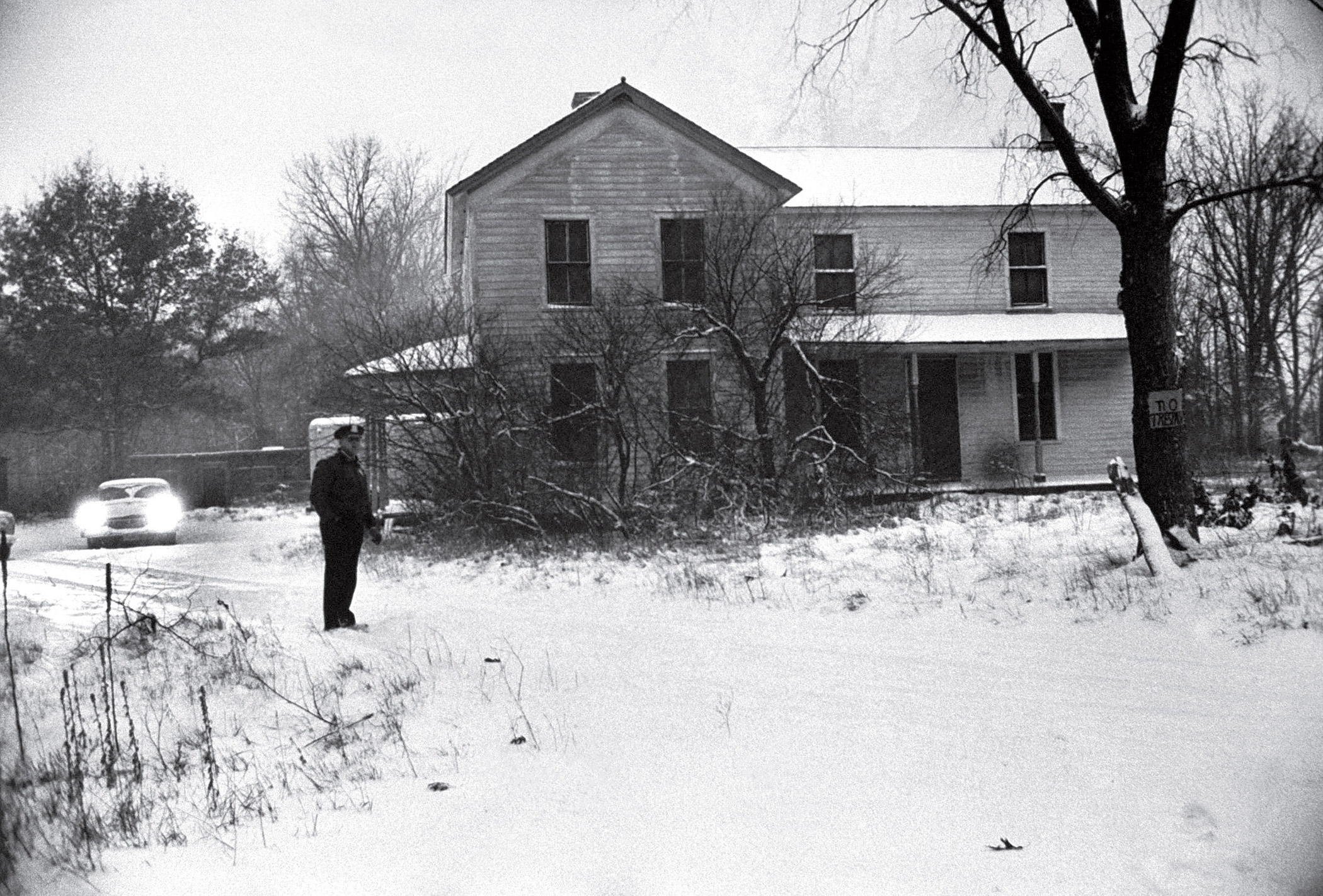 Deputy sheriff standing outside of house belonging to alleged mass murderer (serial killer) Ed Gein, where he lived a deceptively quiet life and where parts of his victim's bodies were found in Plainview, Wisc.