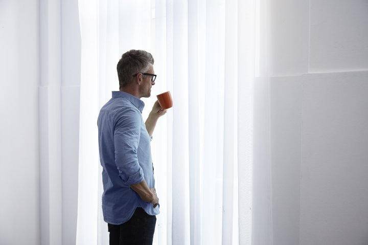 man-looking-out-window-holding-cup