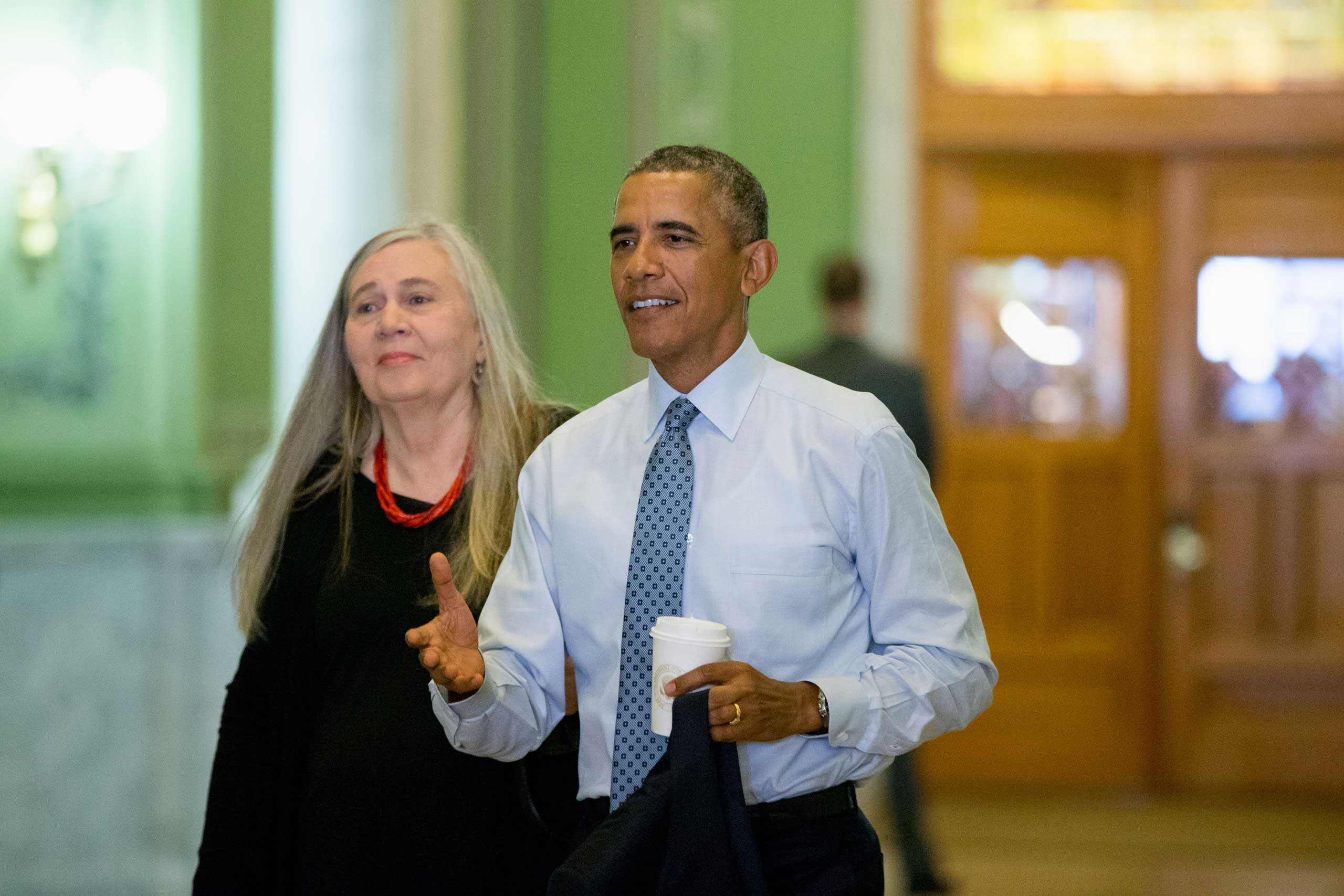 President Barack Obama, accompanied by Pulitzer Prize winning Iowa writer Marilynne Robinson, arrives to the State Library of Iowa in the Ola Babcock Miller Building in Des Moines, Sept. 14, 2015.