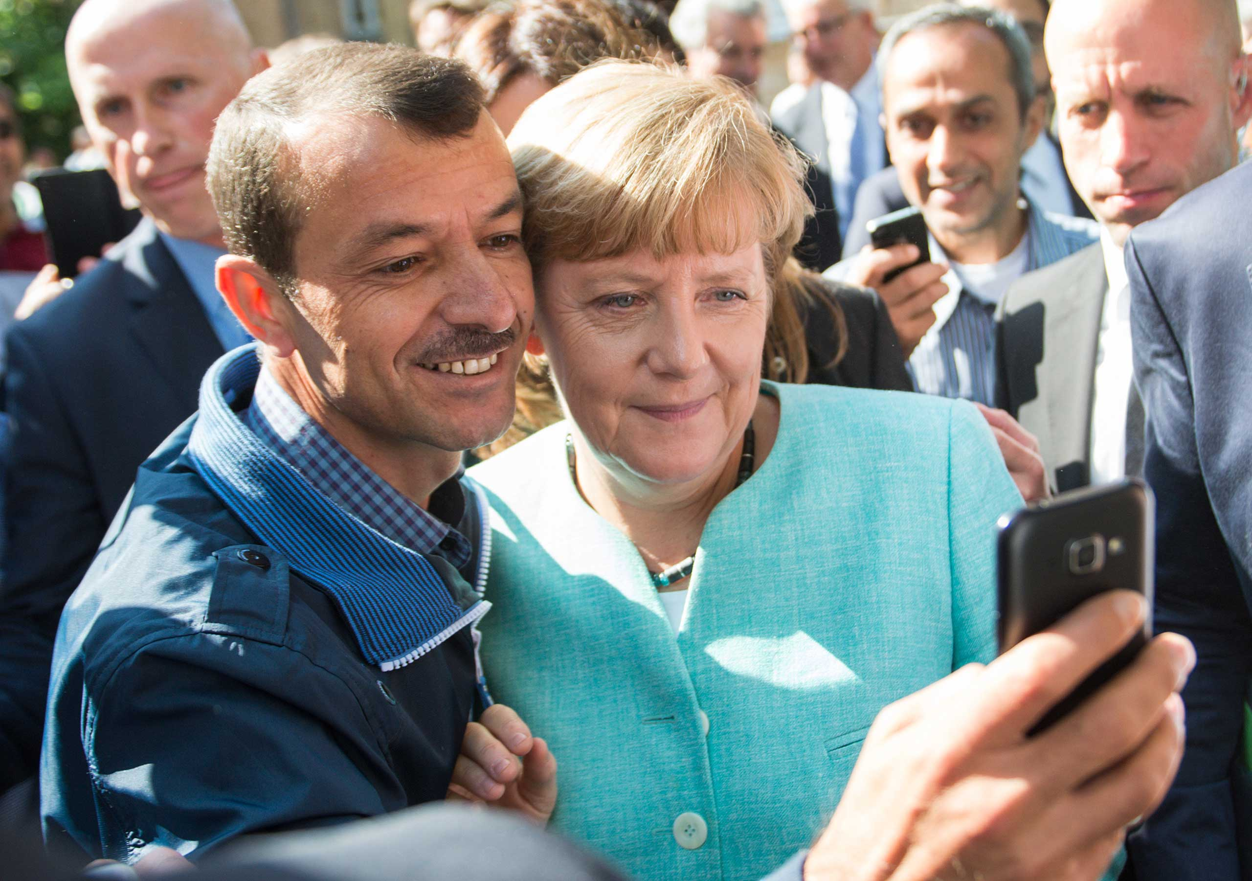 German Chancellor Angela Merkel (R) has a selfie taken with a refugee during a visit to a refugee reception centre in Berlin, 10 Sept. 2015.