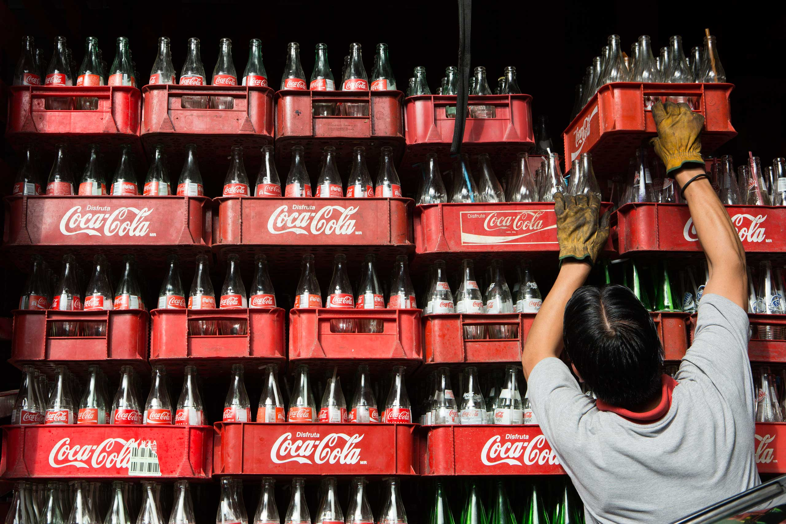 A worker loads a delivery truck with empty Coca-Cola bottles in Mexico City in 2013.