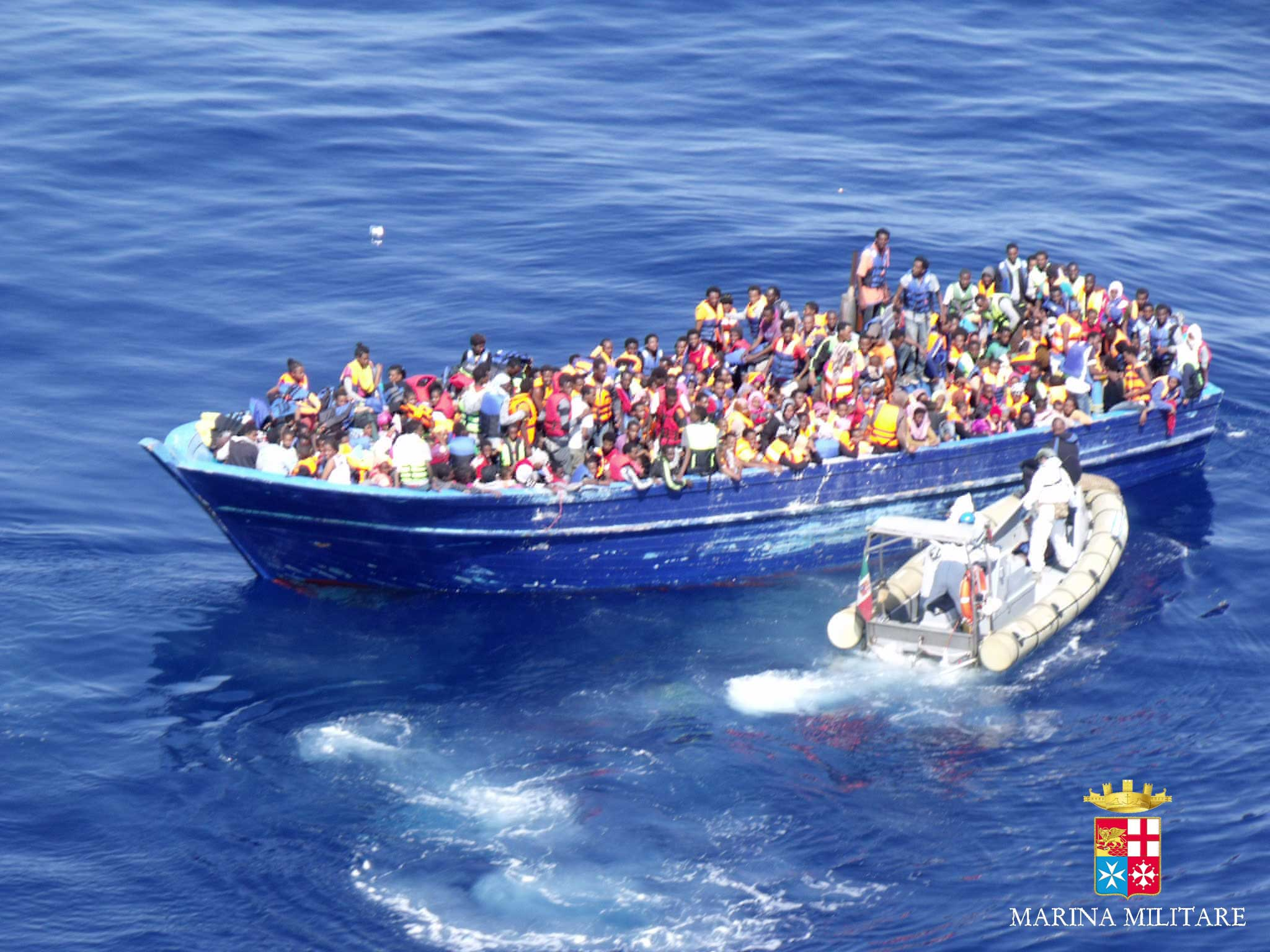 Migrants are approached by an Italian Navy dinghy boat, in the Mediterranean sea, on Aug. 22, 2015.