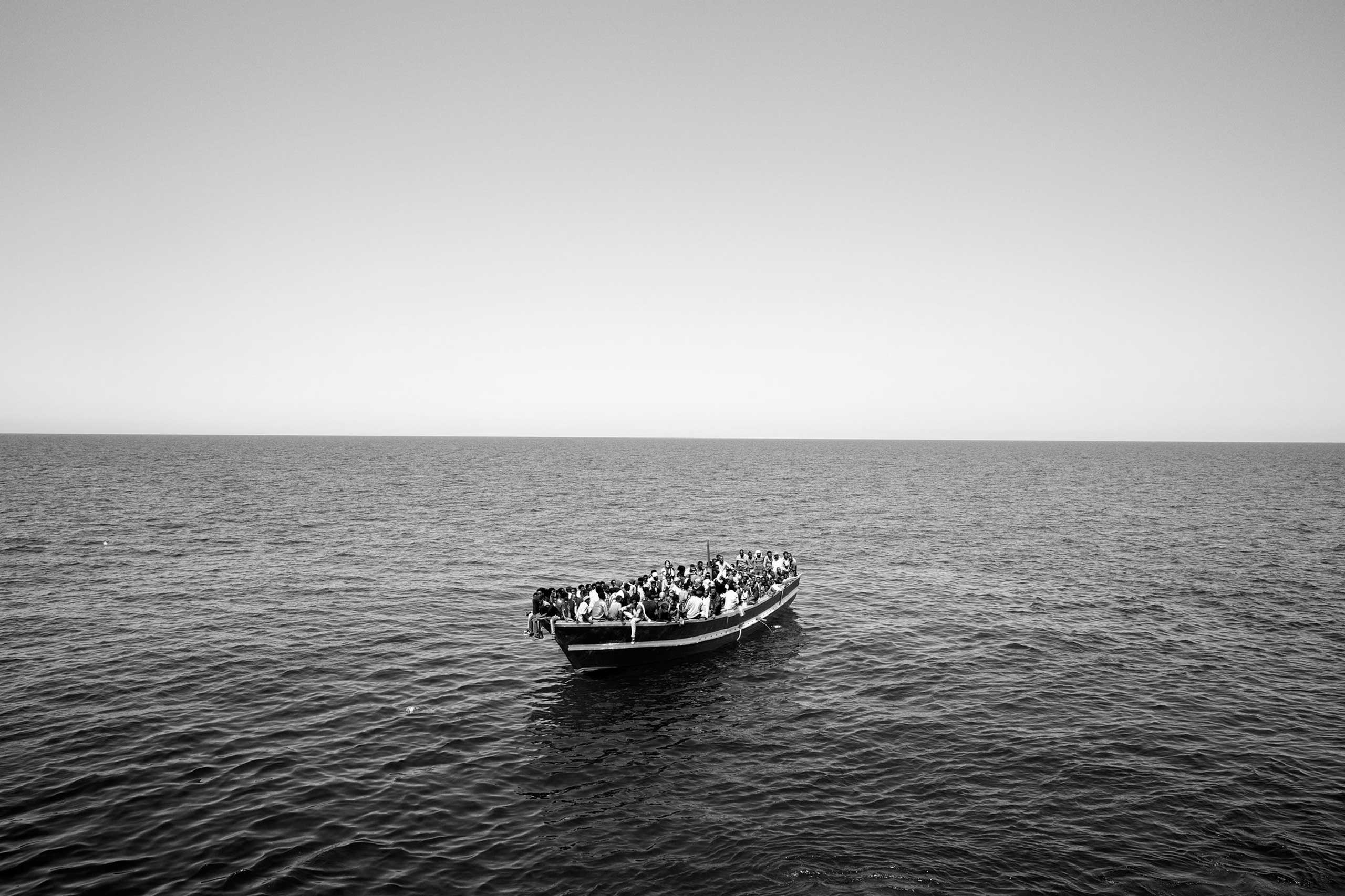 The New York Times Magazine: Desperate CrossingMigrants about to be rescued by Médecins Sans Frontières (Doctors Without Borders) from a fishing boat drifting across the Mediterranean Sea off the coast of Libya, on July 2015.