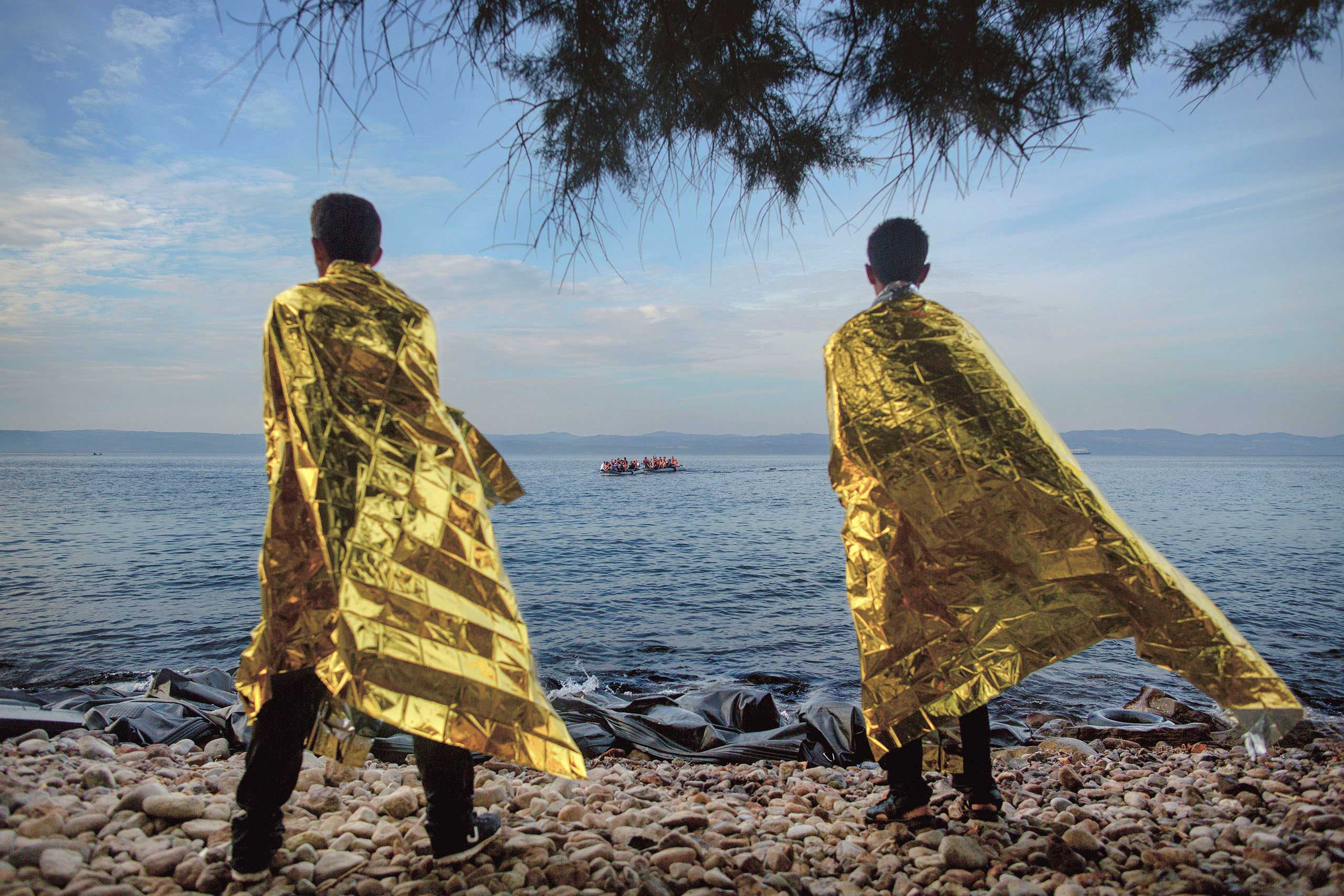 Verdens Gang:  Escape From War                               Two men who have arrived on the Greek island of Lesbos use foil blankets to keep warm  as they watch Syrian refugees approaching the beach, Sept. 9, 2015.