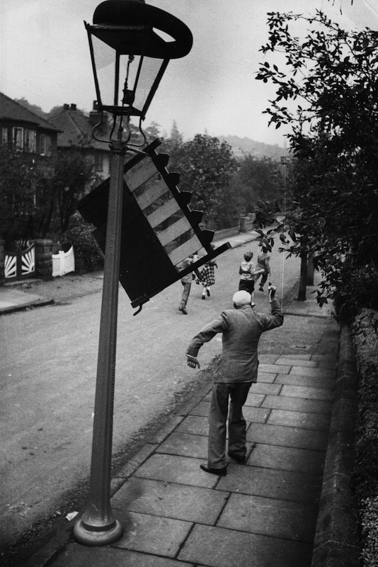 An irate householder waving his fist at a group of mischief makers who hung his garden gate on a lamppost to celebrate Leeds Mischief Night, before Guy Fawkes Day, in 1954.