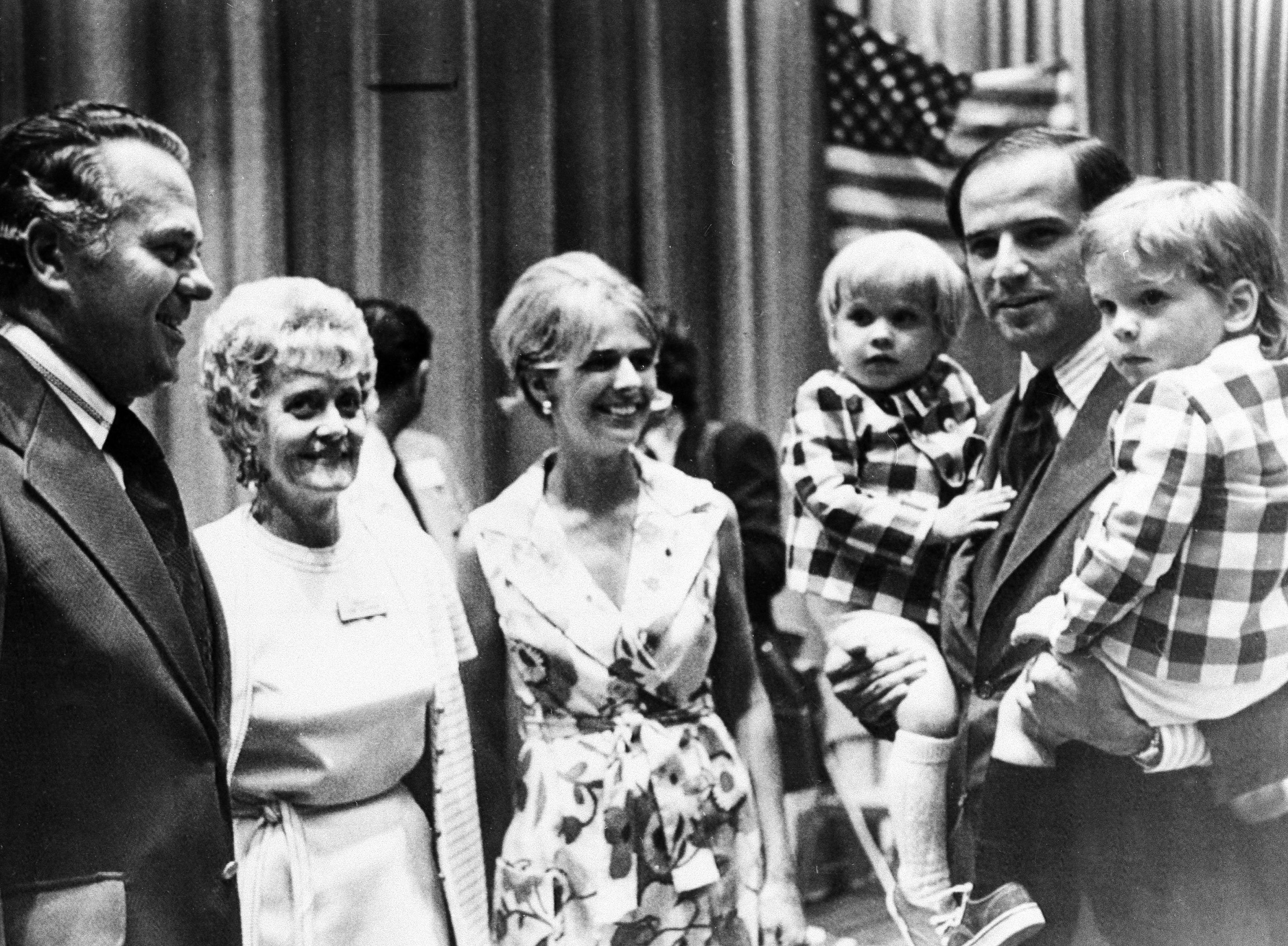 Senator Joe Biden  carries both of his sons, Joseph R. III (left) and Robert H. (right) during an appearance at the Democratic state convention in 1972.  At center is his first wife Neilia.