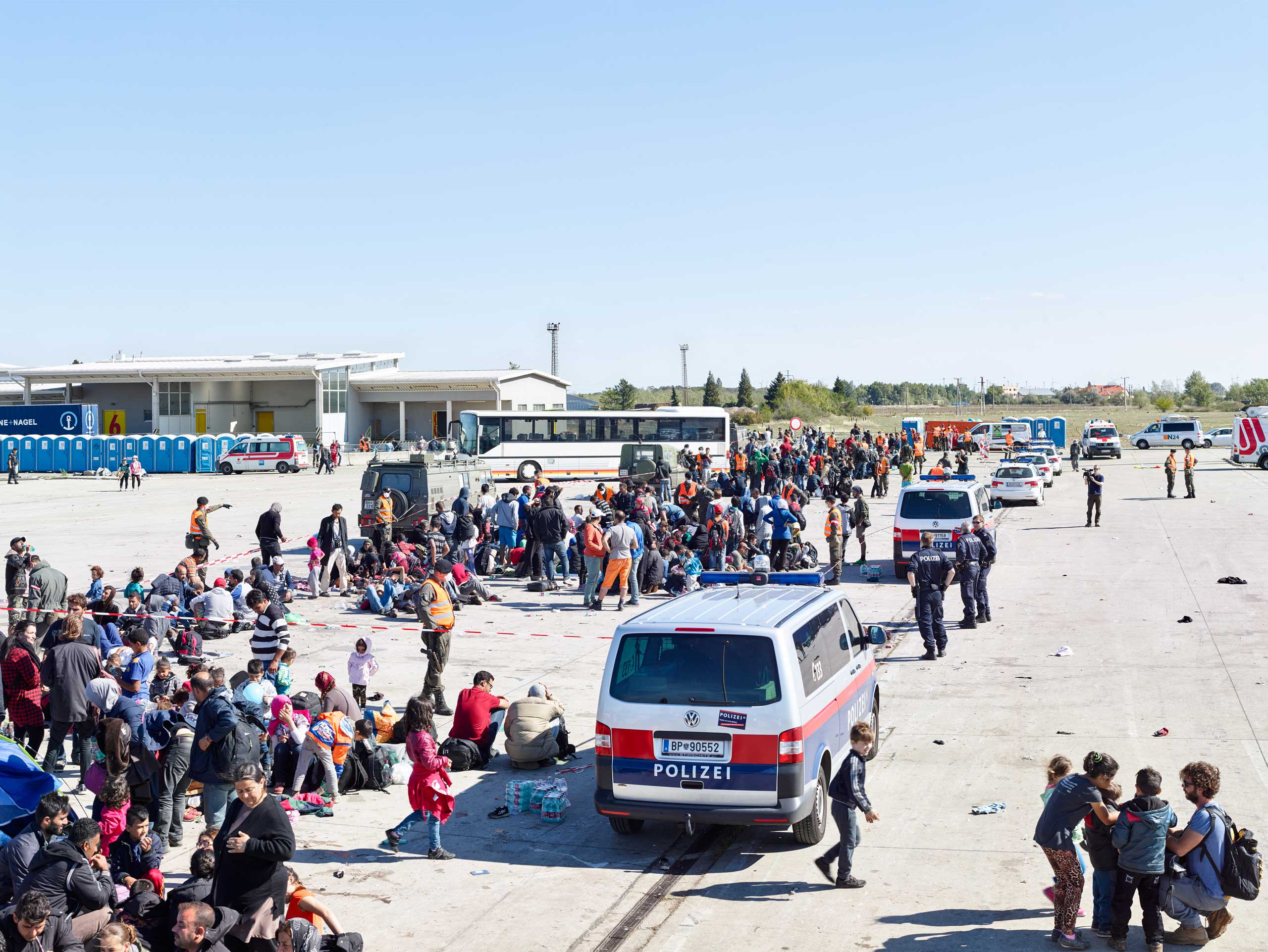 Refugees wait in Nickelsdorf, Austria, on the Hungary border, for buses to take them further into Europe.