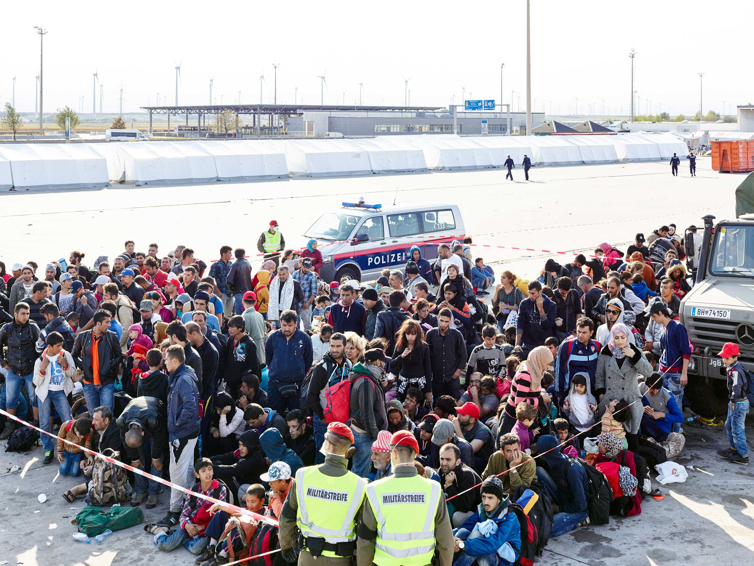 Austrian police and army personnel in Nickelsdorf organize groups of migrants as they prepare to be loaded onto buses to take them further into Europe.