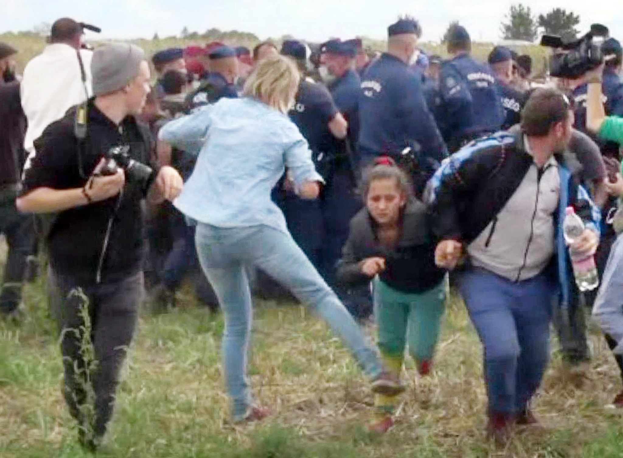 This video grab made on Sept. 9, 2015 shows Petra Laszlo kicking a child as she run with other migrants from a police line during disturbances in Roszke, southern Hungary.