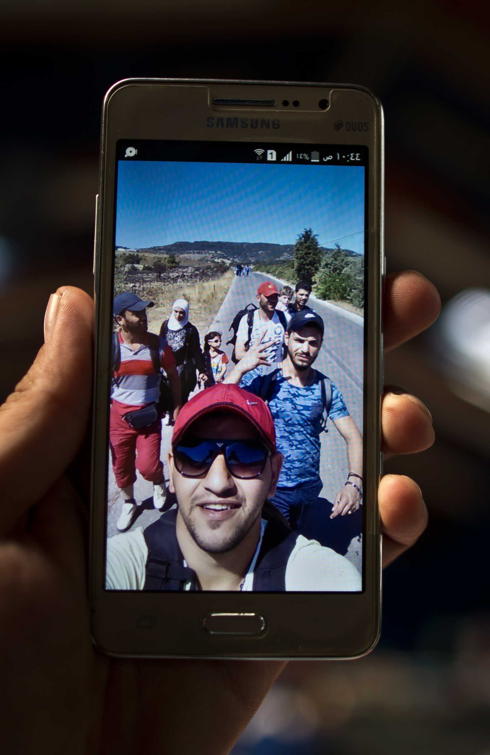 A migrant, shows a selfie of himself in blue shirt and friends somewhere in the Balkans,  after he spent the night in a shelter near Graz, Austria. Sept. 22, 2015.