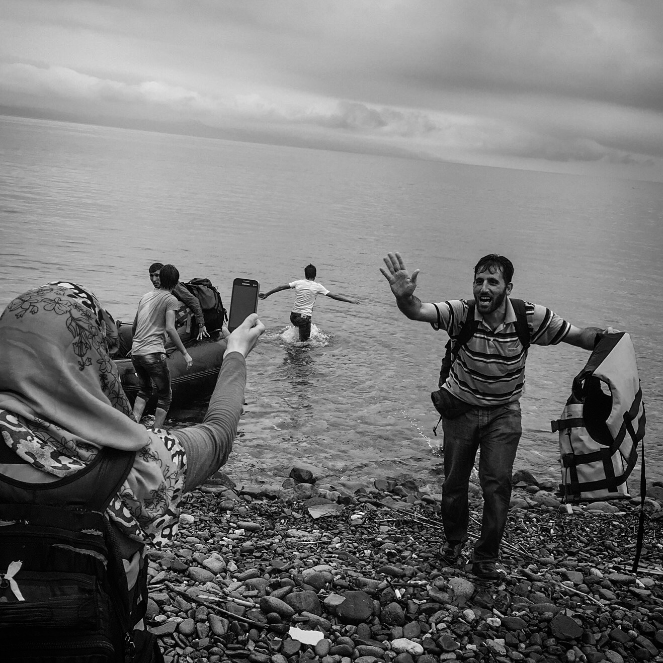 Refugees take photos on their cellphones after arriving on the island of Lesbos in Greece.