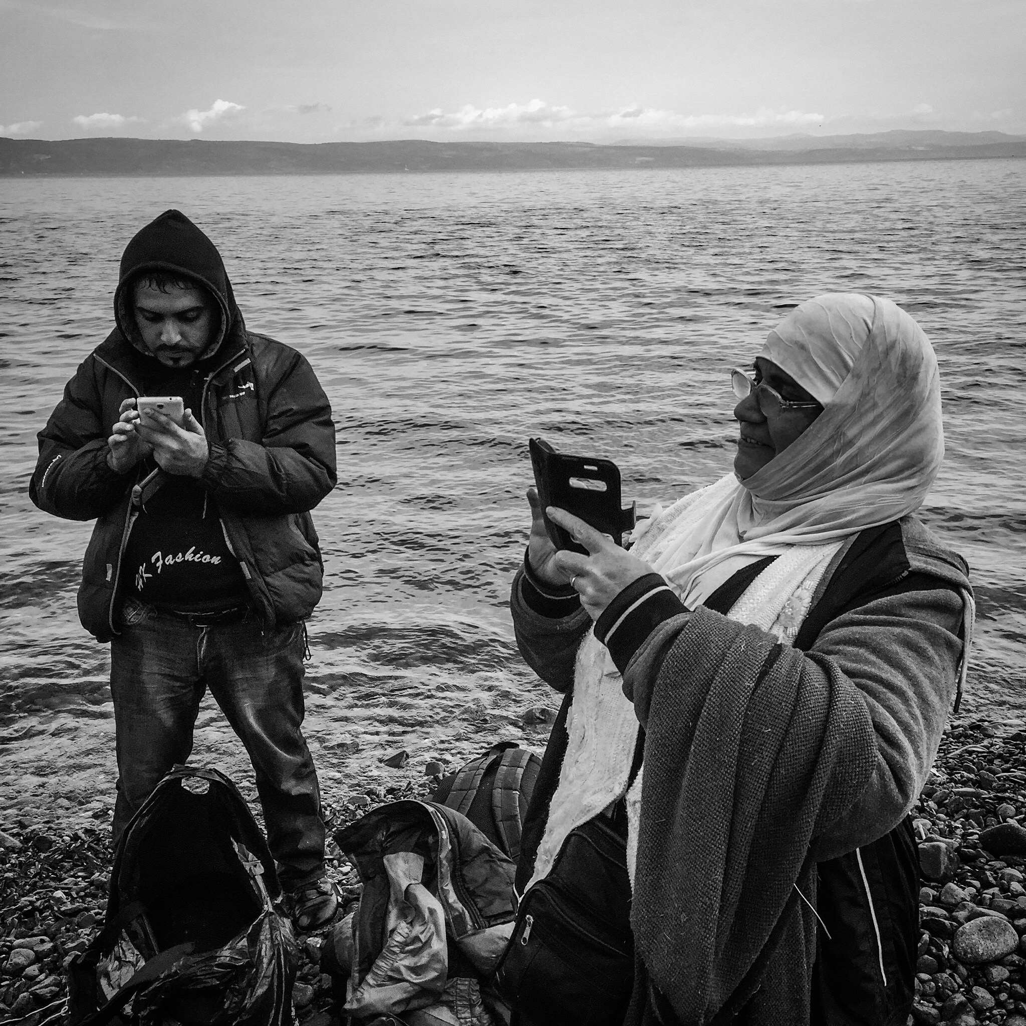 Refugees take photos and send messages on their cellphones after arriving on the island of Lesbos in Greece.