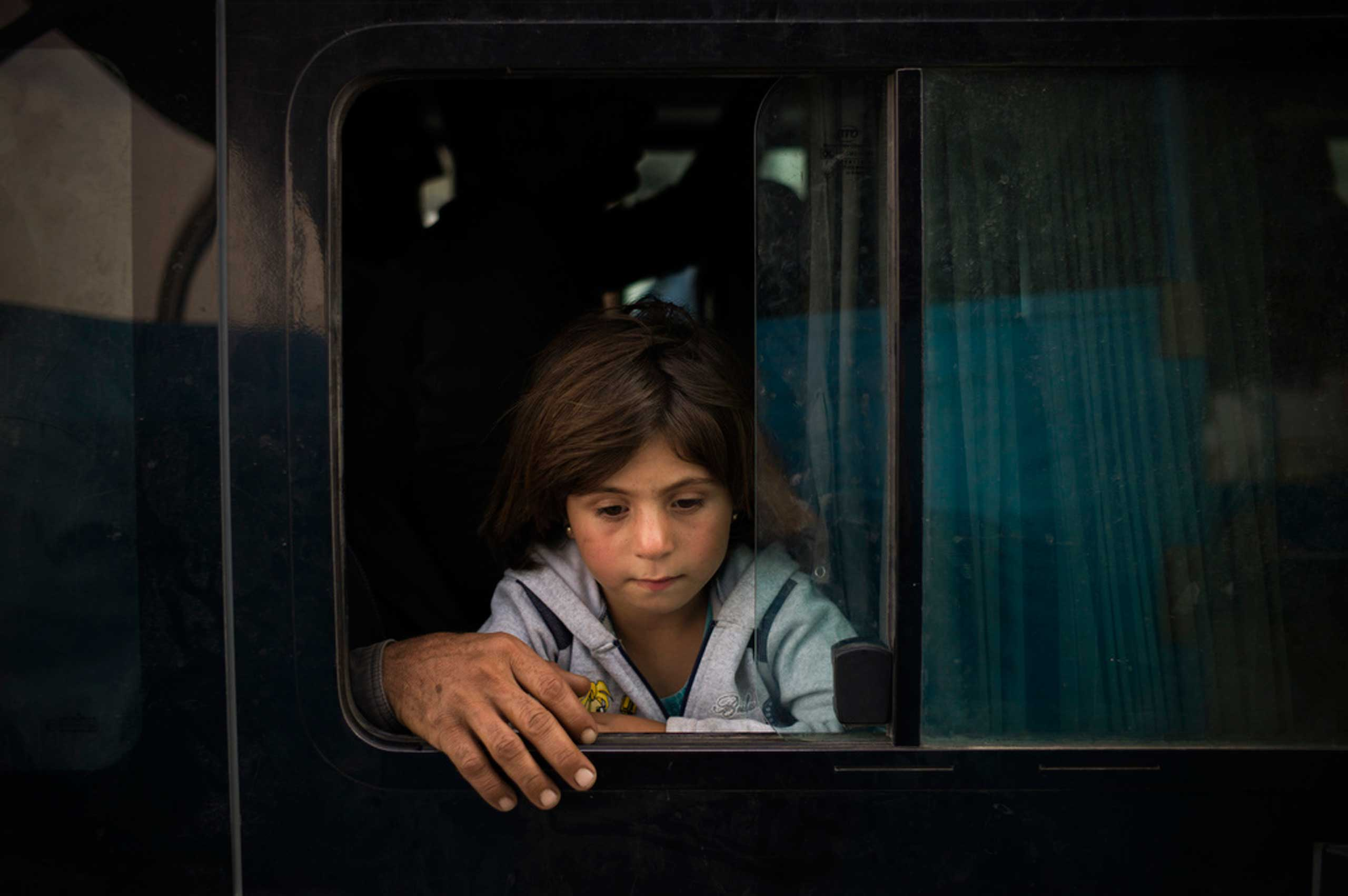 A young Syrian girl from Kobani is seen inside a bus arriving at a new transit point at the Ibrahim Khalil Border Crossing in Iraq after traveling by bus from Turkey. Oct. 2014