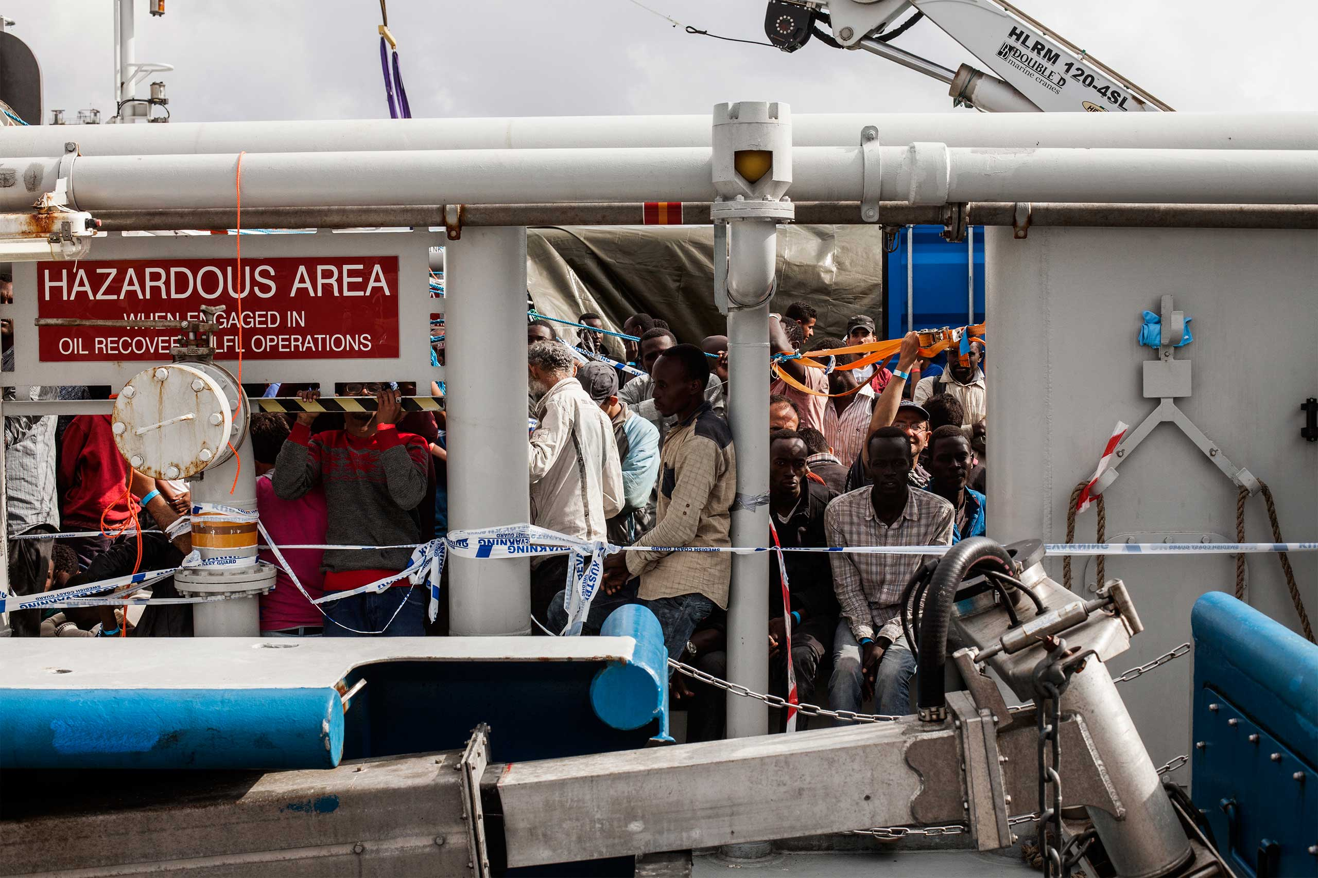 A group of African and Syrian refugees and migrants wait on a Swedish ship before disembarking in the Sicilian city of Catania. June 2015.