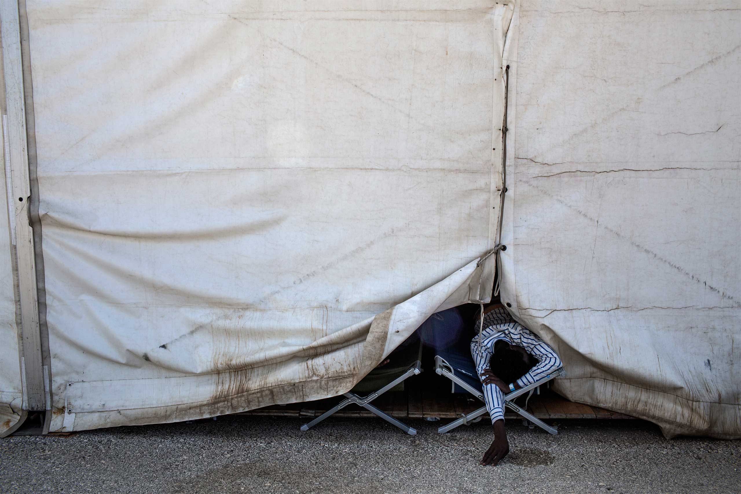 A Sudanese refugee who fled from Darfur rests on a cot in a reception facility of Augusta, Sicily. June 2015.