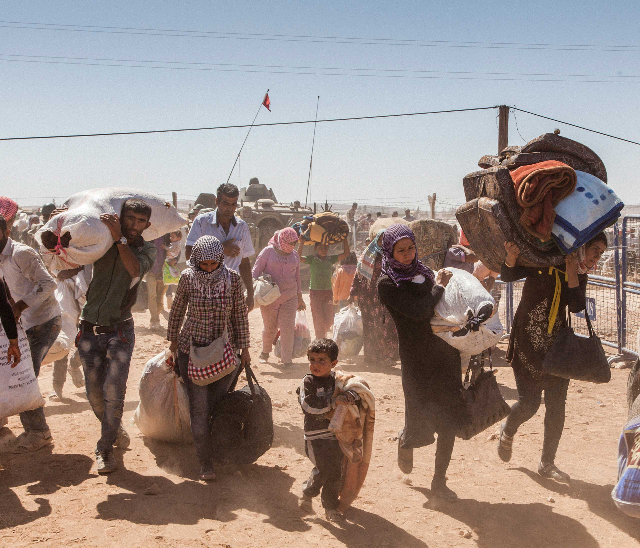 Syrian refugees cross the border from Syria into Turkey after fleeing fighting between Kurdish forces and ISIS around the city of Kobane in North East Syria. Sept. 2014.