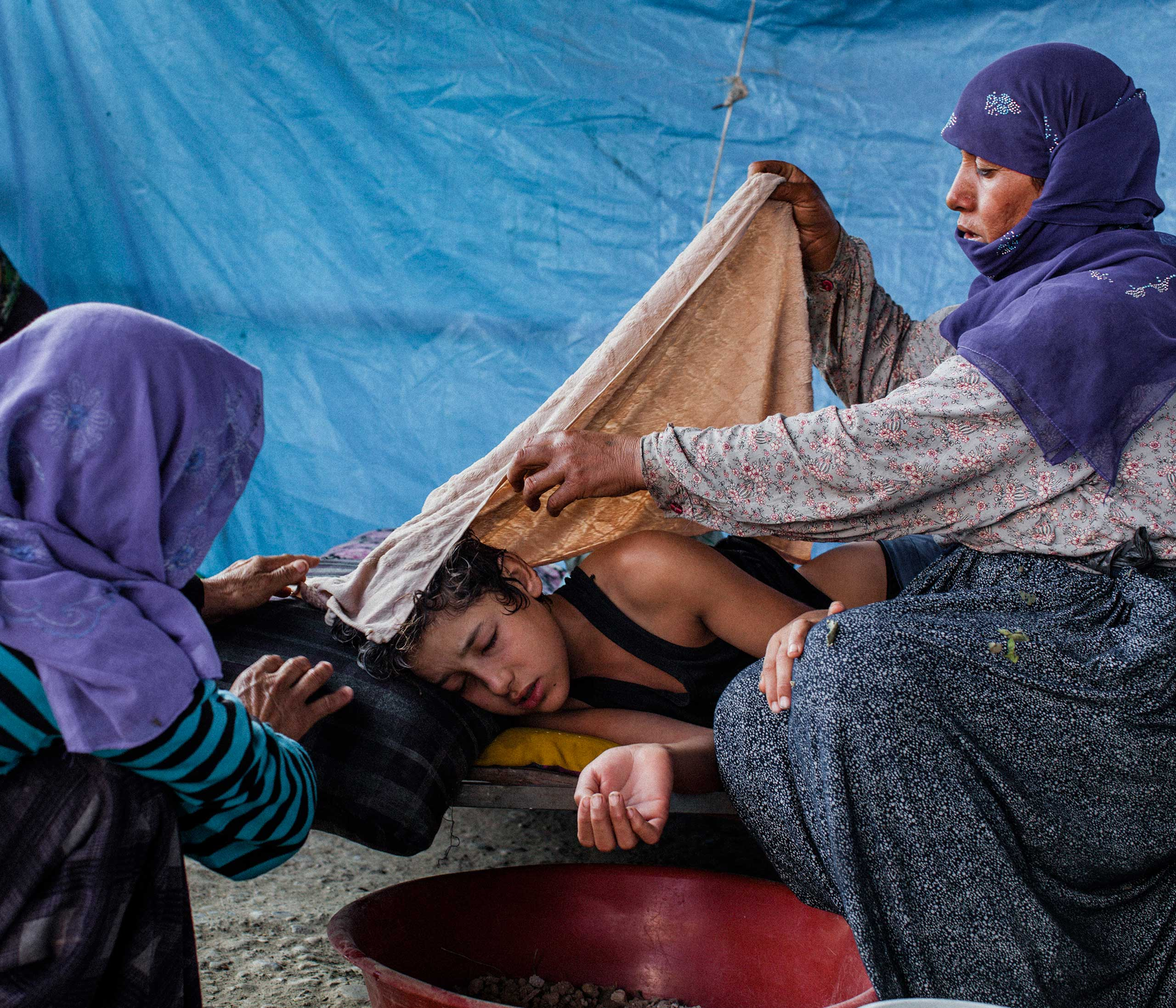 Nizal (14) is tended to by his mother (right) and a relative, after falling ill with a high fever and vomiting. The family was living in a small tented area on the outskirts of Adana in southern Turkey after fleeing Syria. Aug. 2014.