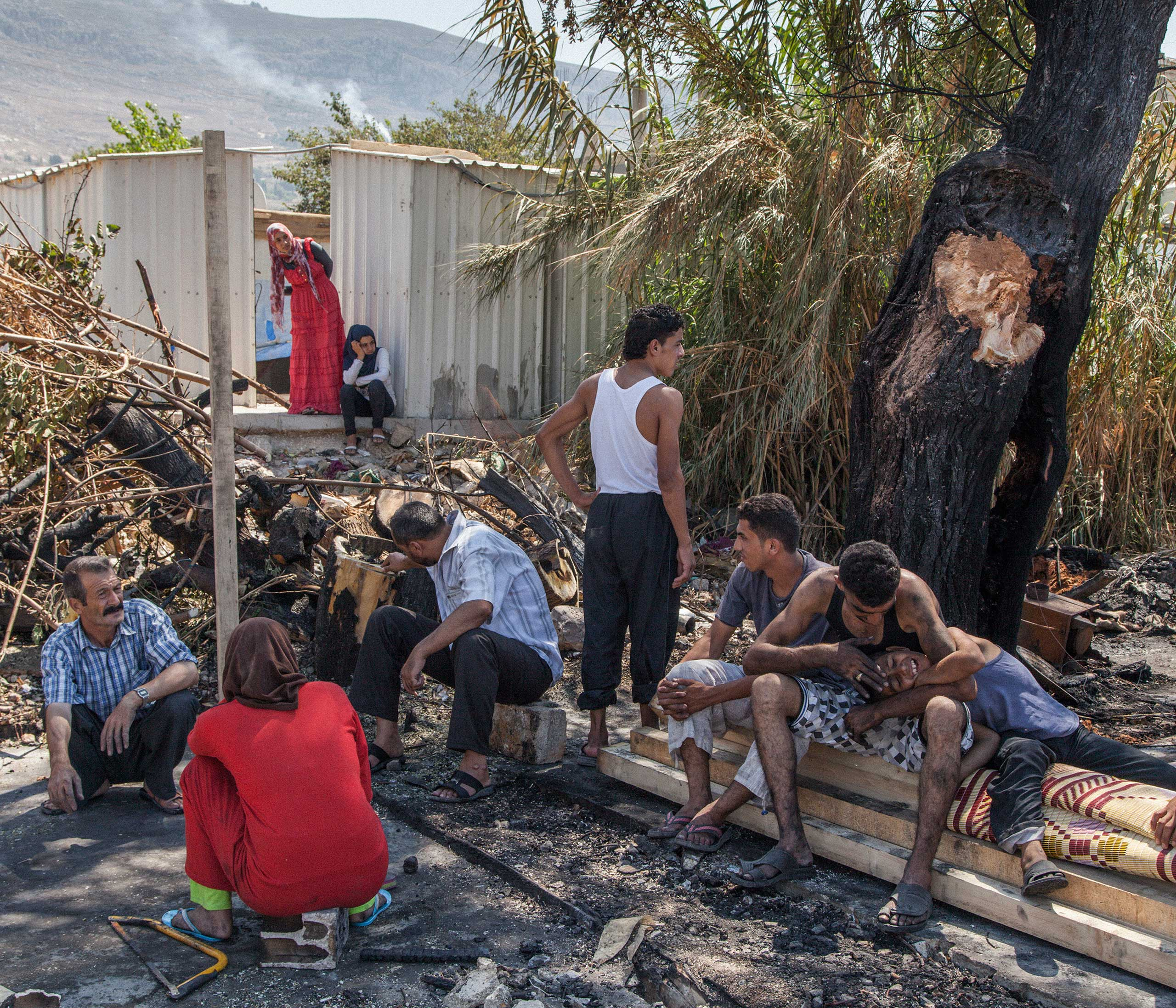 The Al-Rashid family, from Hama in Syria, sit amongst the ashes of their shelter. A fire the previous day destroyed all of the 25 tents that stood in the Al-Rashid camp on the outskirts of Minieh in Northern Lebanon, a town on the border with Syria. Aug. 2014.