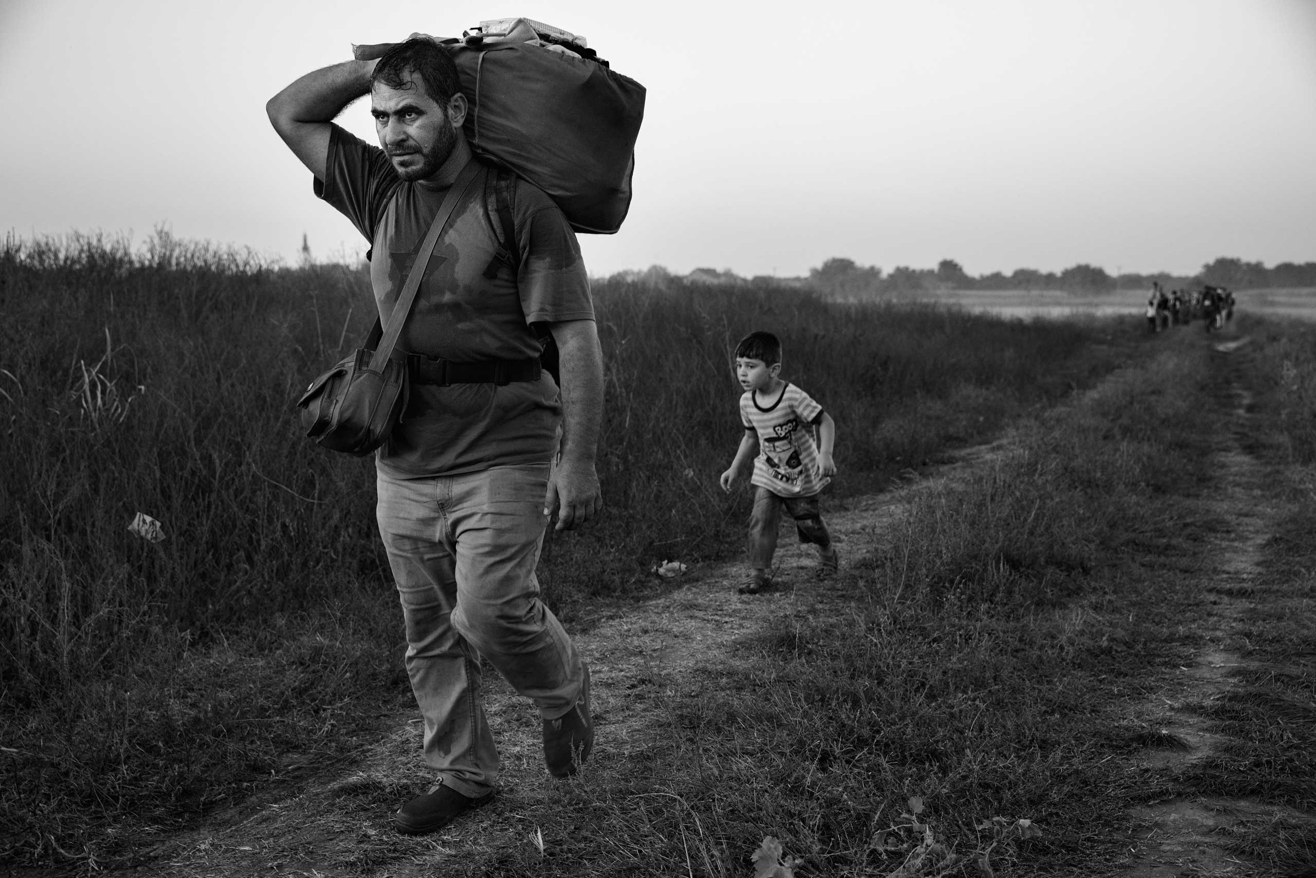 A man walks with his son behind him as they make their way to the train station in Tovarnik, Croatia, on the border with Serbia. In the Balkans, many migrants began traveling by foot, echoing more ancient journeys, Sept. 17, 2015.