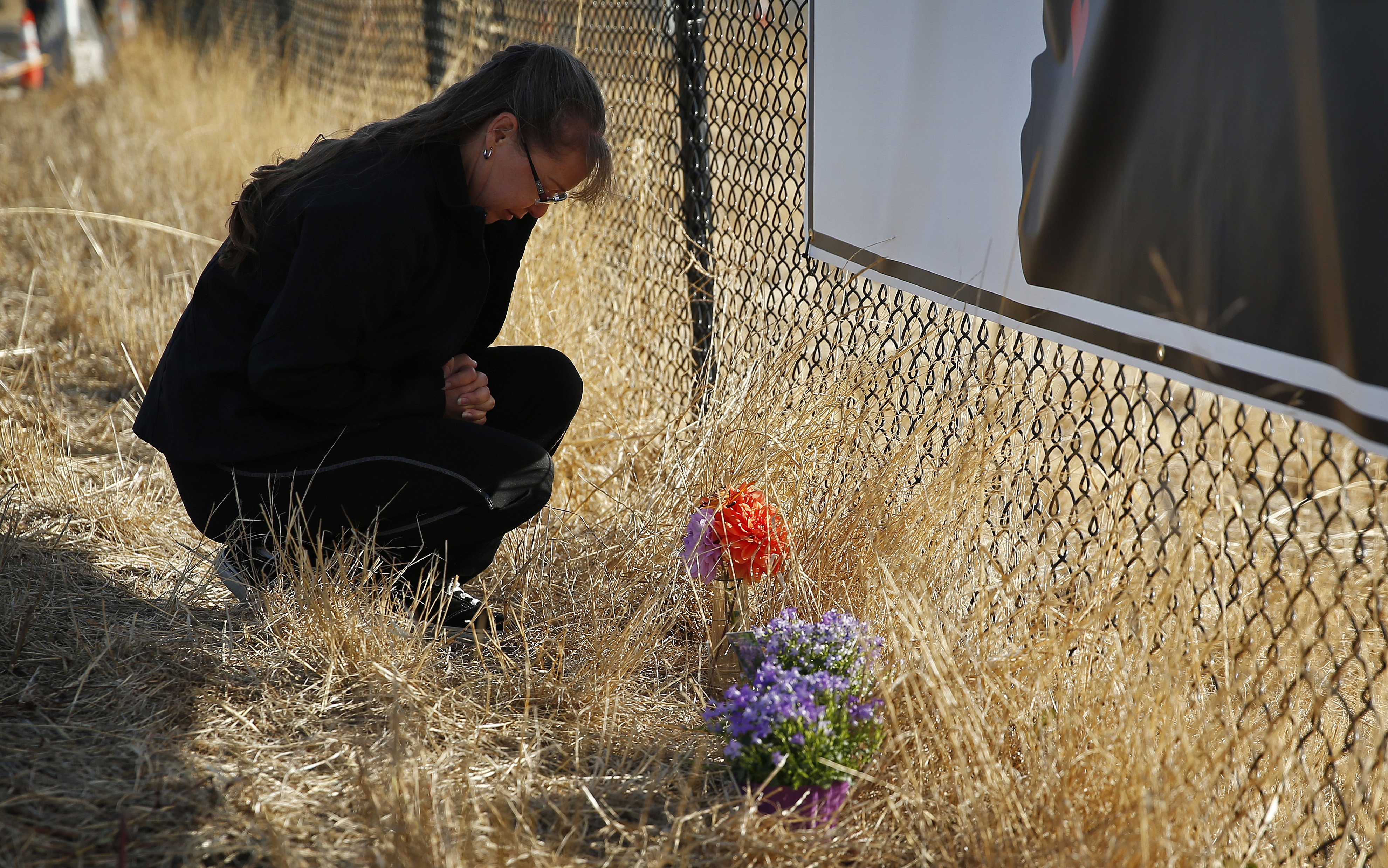 Robin Griffiths, of Portland, prays at a makeshift memorial near the road leading to Umpqua Community College on Oct. 3, 2015, in Roseburg, Ore.
